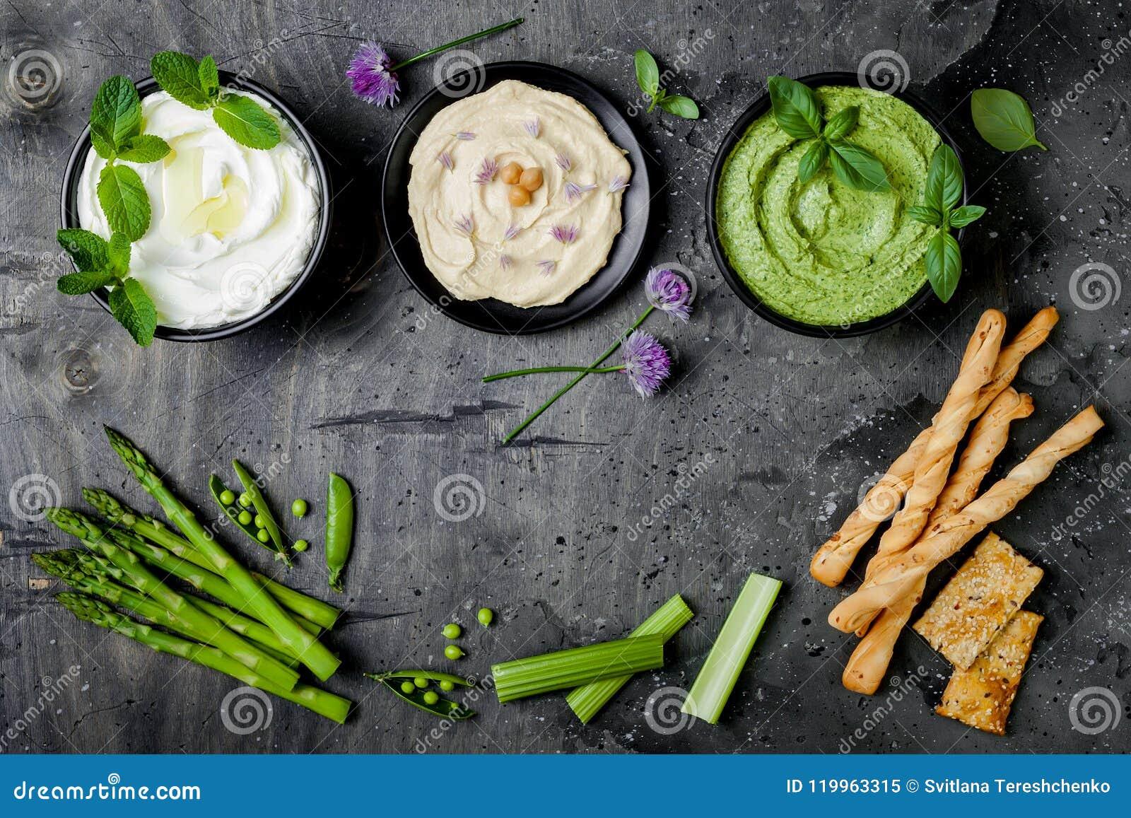 Tablero crudo del bocado de las verduras verdes con las diversas inmersiones Salsa o labneh, hummus, hummus o pesto con las galle