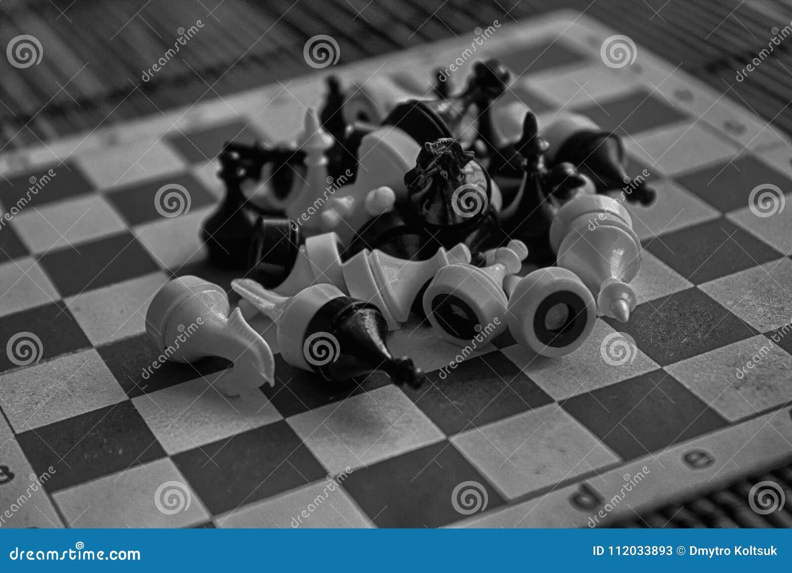 Tablero de ajedrez de madera monocromático y pedazos de ajedrez plásticos magnéticos, a bordo