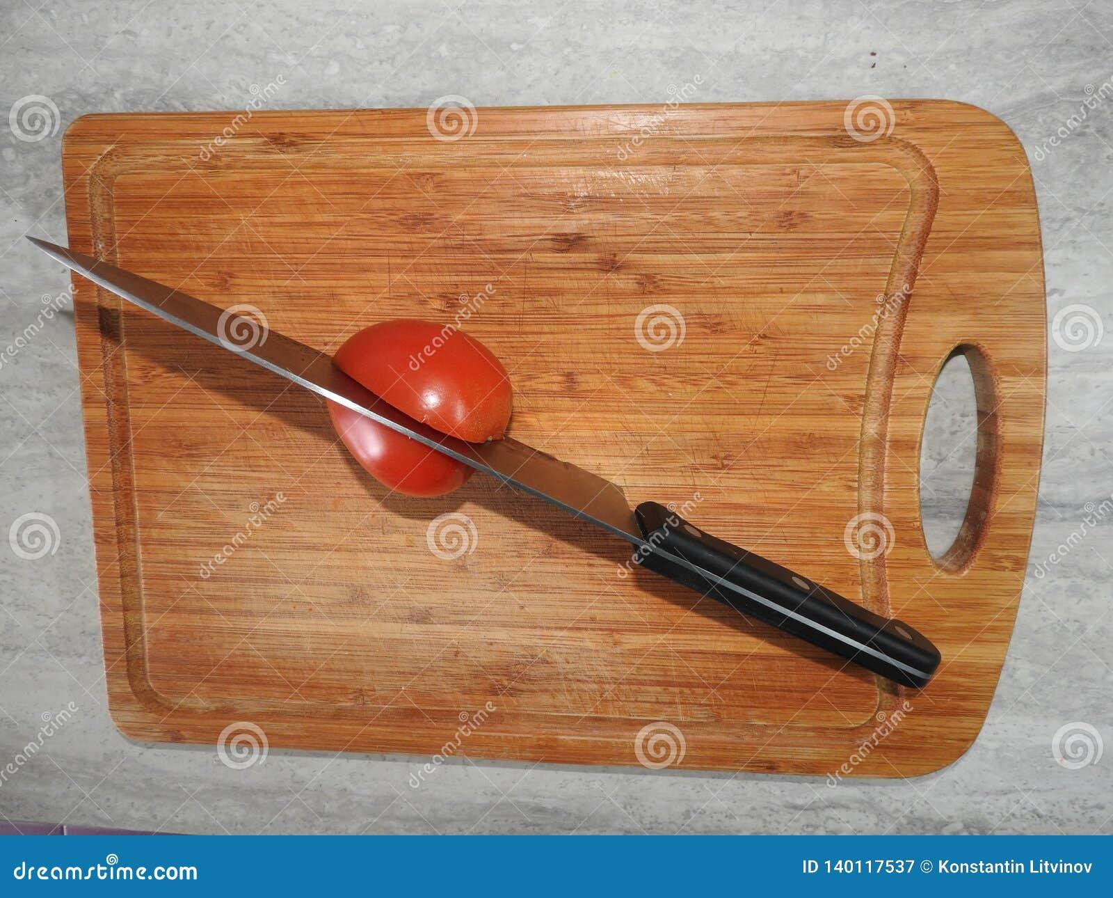 Tablero de madera para cortar las comidas en la tabla en la cocina