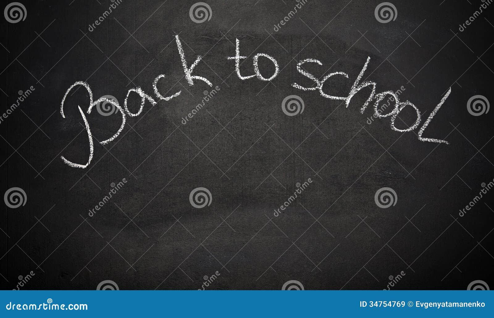 Tablero de tiza de la escuela con palabras de nuevo a escuela