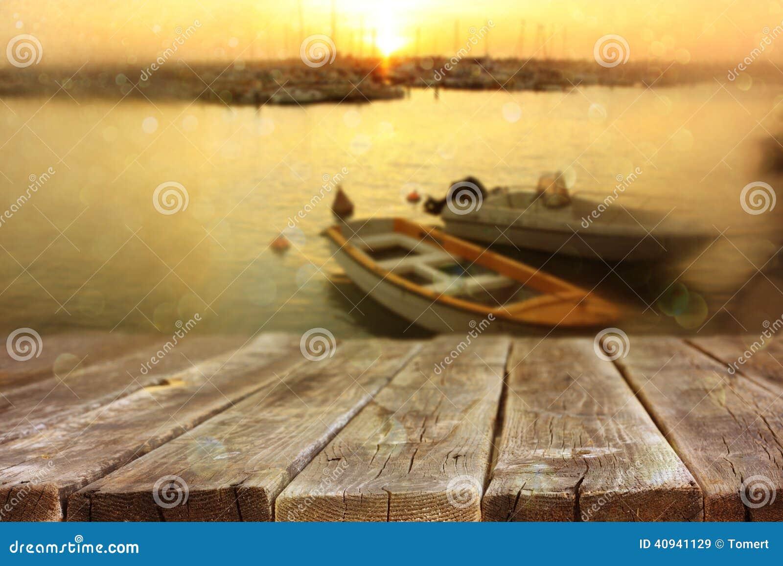 Tableros de madera delante del paisaje del mar y de los barcos de pesca