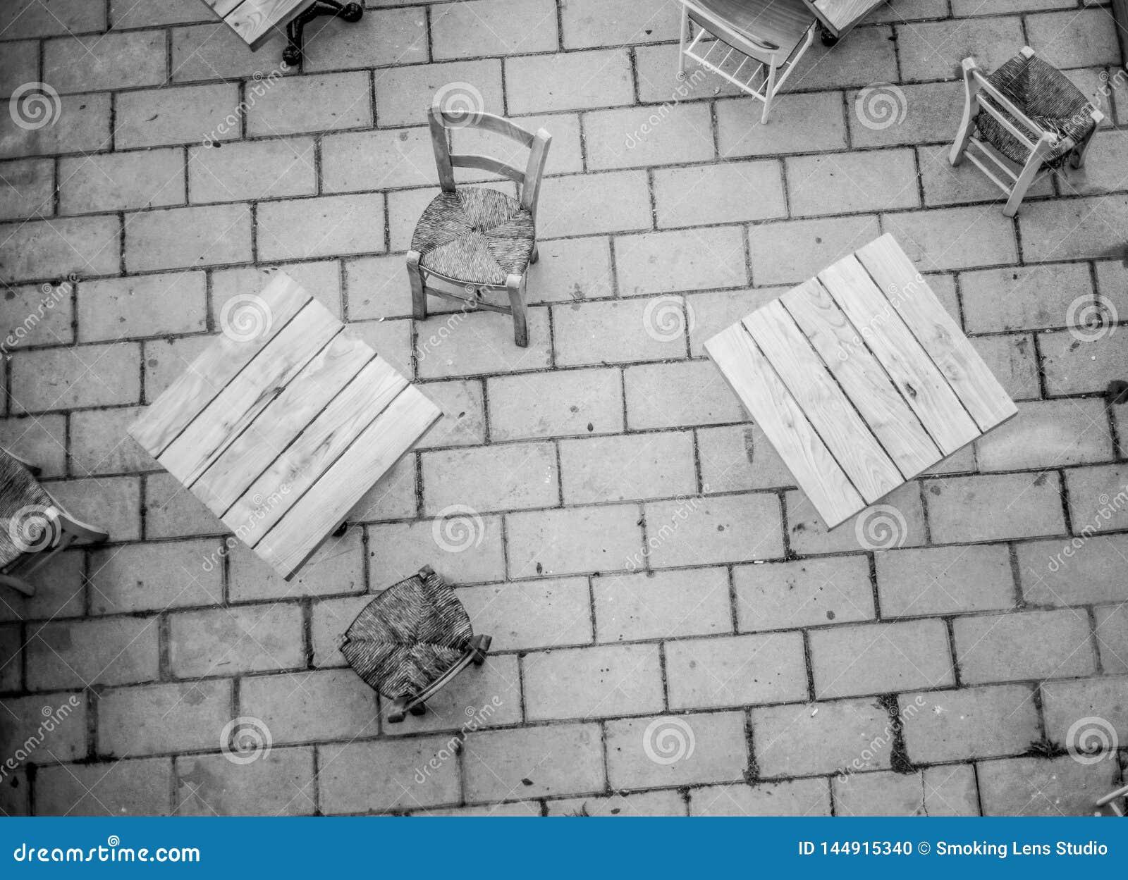 Tables basses en haut dedans de noir et blanc dans une rue piétonnière