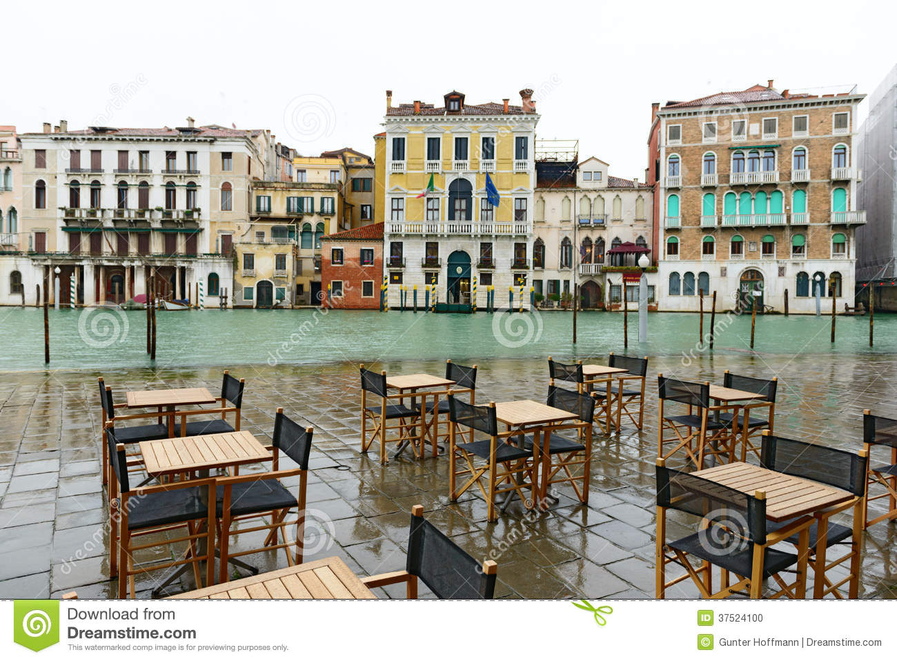 Tables And Chairs Near Canal Grande At High Tide In Winter (Venice, Italy)
