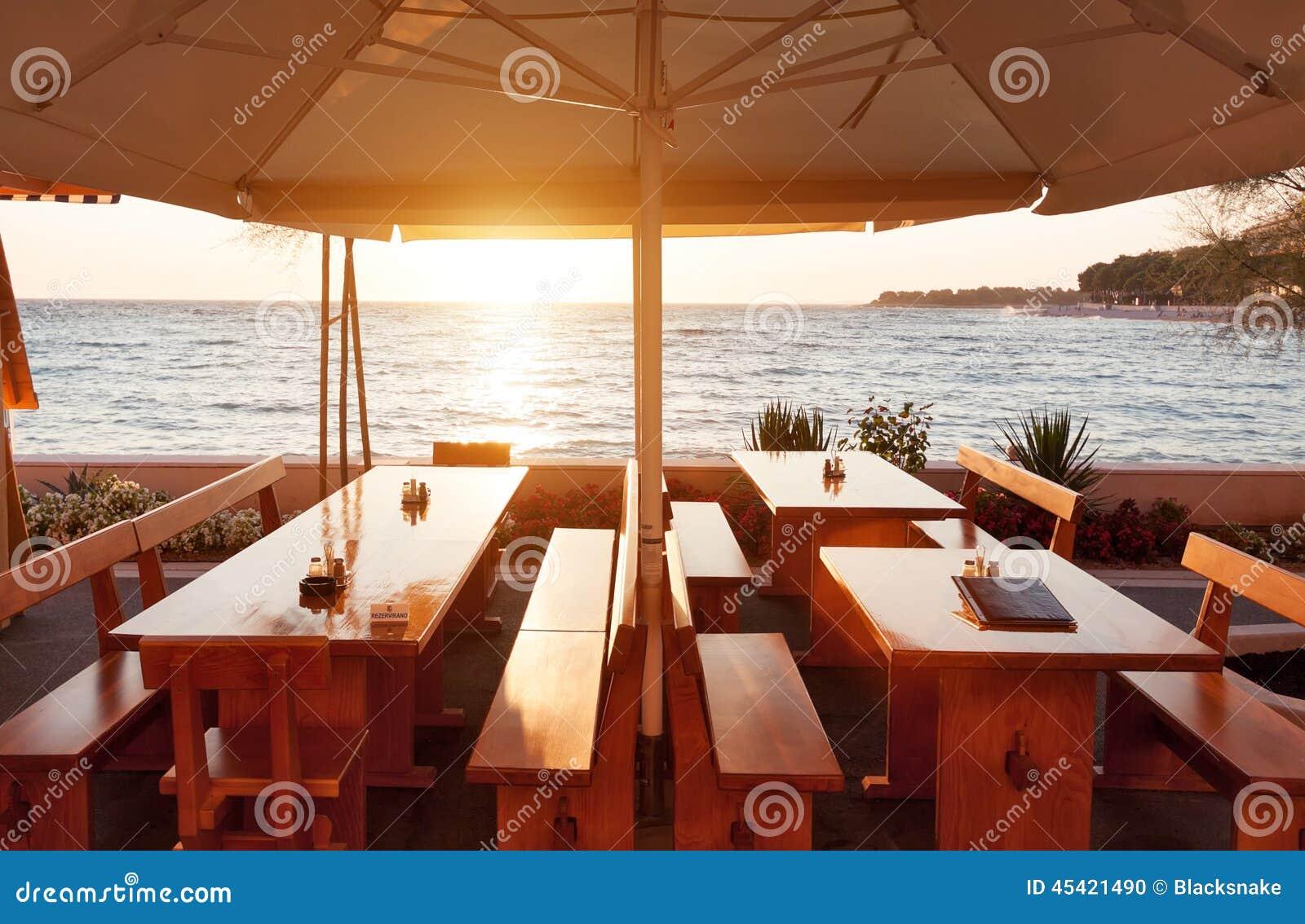 tables de restaurant de terrasse sous le parasol au coucher du soleil photo stock image du. Black Bedroom Furniture Sets. Home Design Ideas