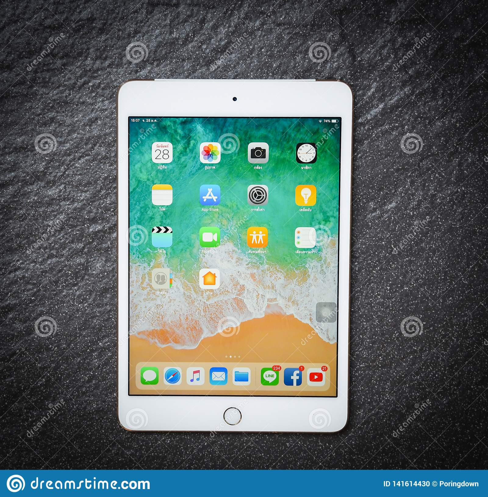 Tablet computer New Apple iPad mini white gold color with display screen front on dark background