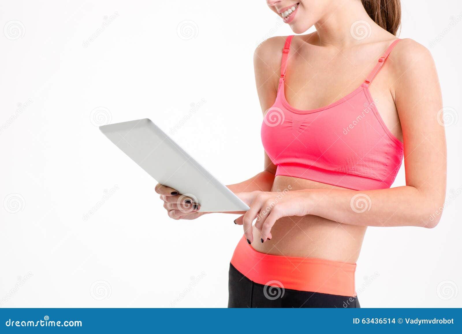 Tablet door slanke mooie jonge sportvrouw wordt gebruikt die