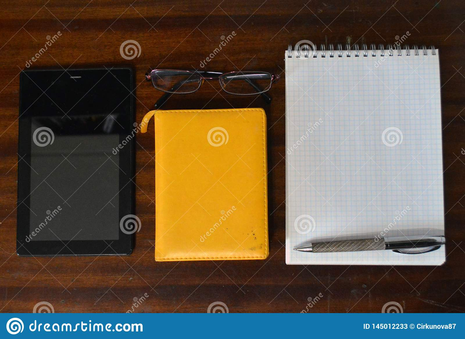 Tablet pc, blocos de notas, vidros e uma pena do metal em uma tabela de madeira escura