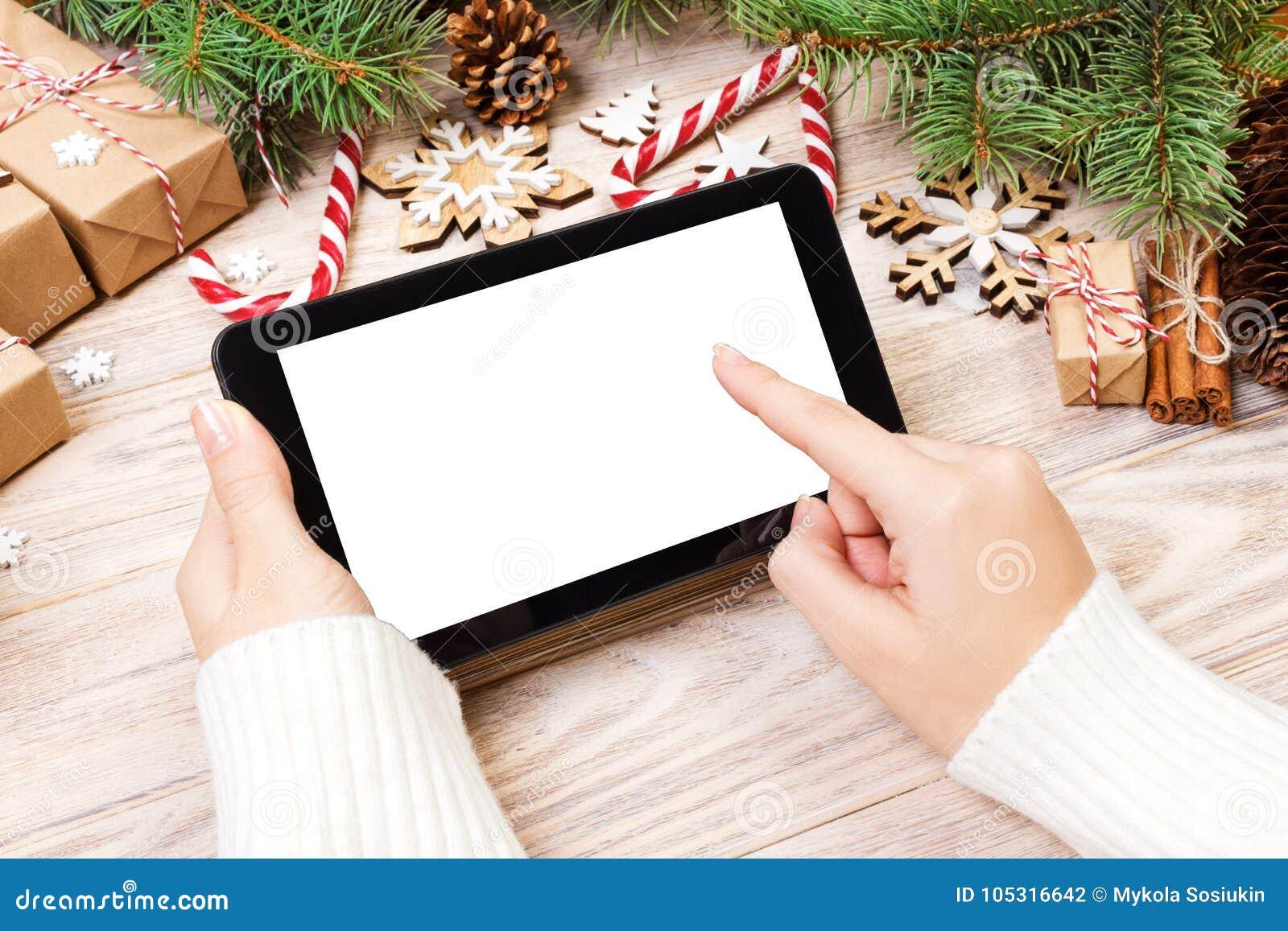 Tablet pc nas mãos da menina o tablet pc com caixa de presente, os doces do Natal e abeto vermelhos ramifica Espaço livre para o
