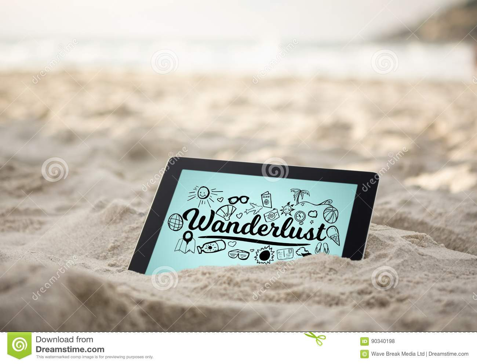 Tablet in sand with black wanderlust doodles against blue background