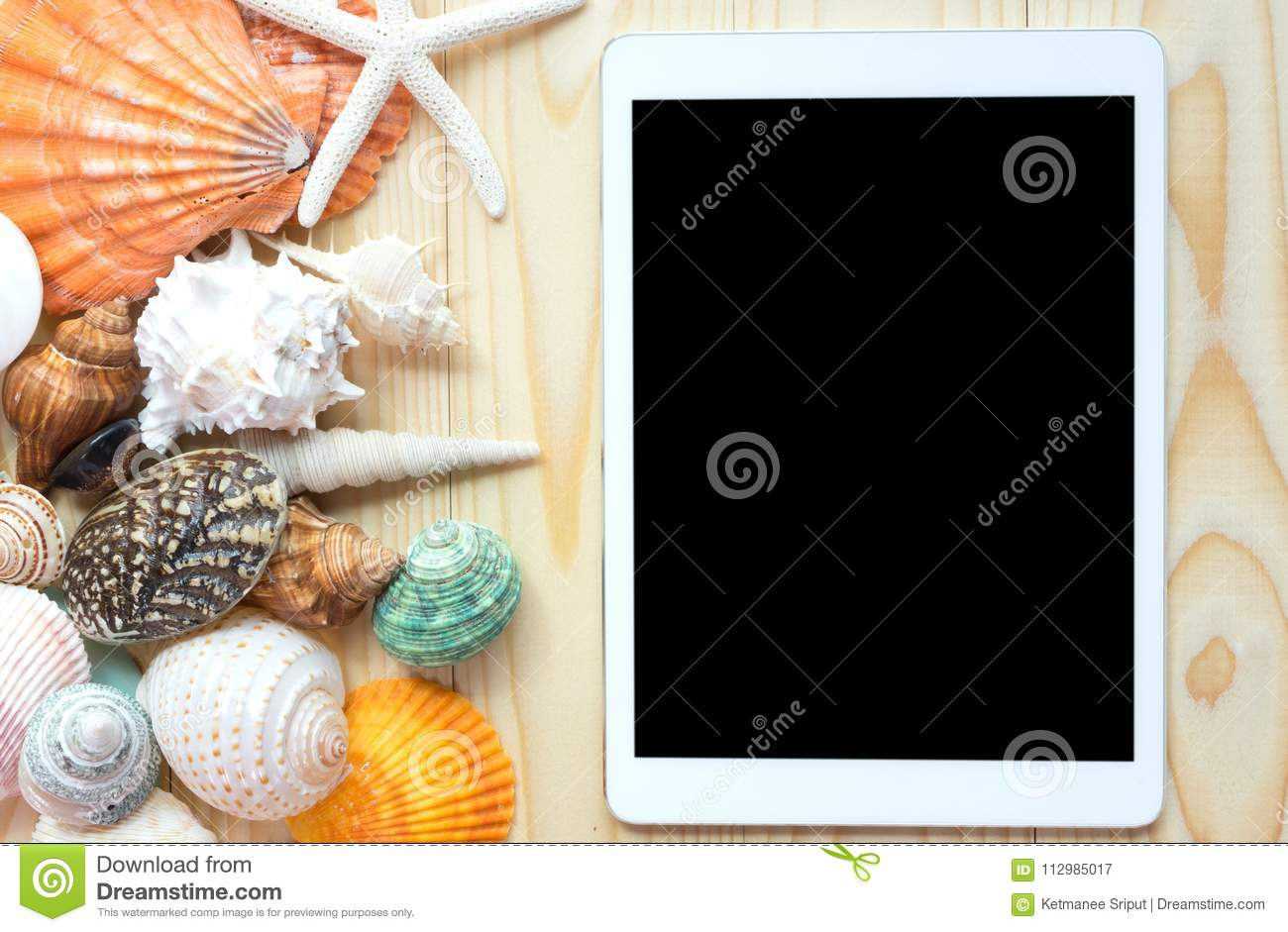 Tablet and seashells on wood background