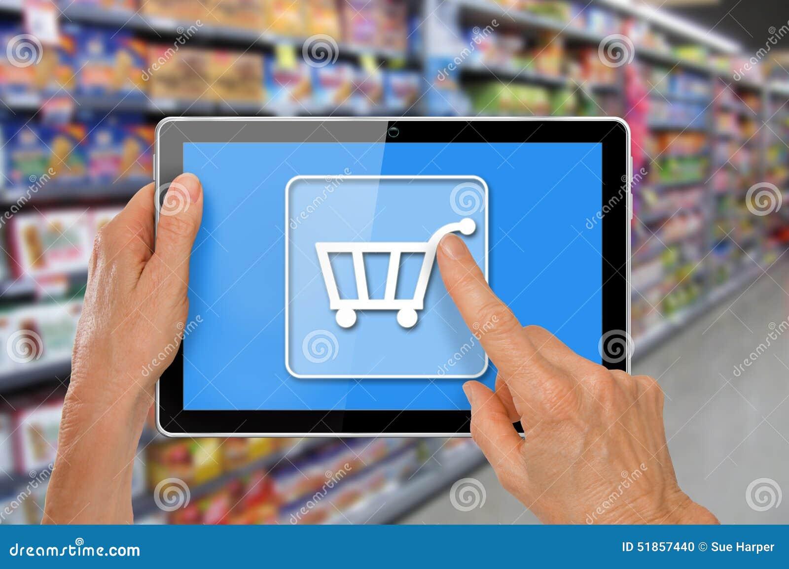 Tableta en línea de las compras del supermercado con las manos