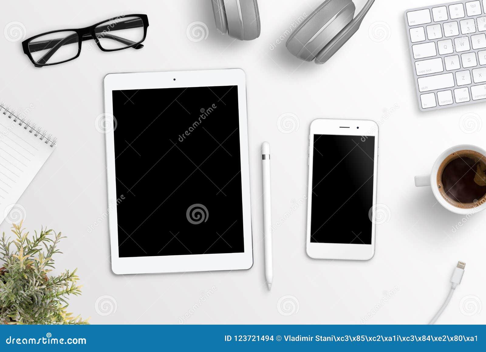Tableta y teléfono en el escritorio de oficina Pantalla en blanco para la maqueta, el app o la presentación responsiva del sitio