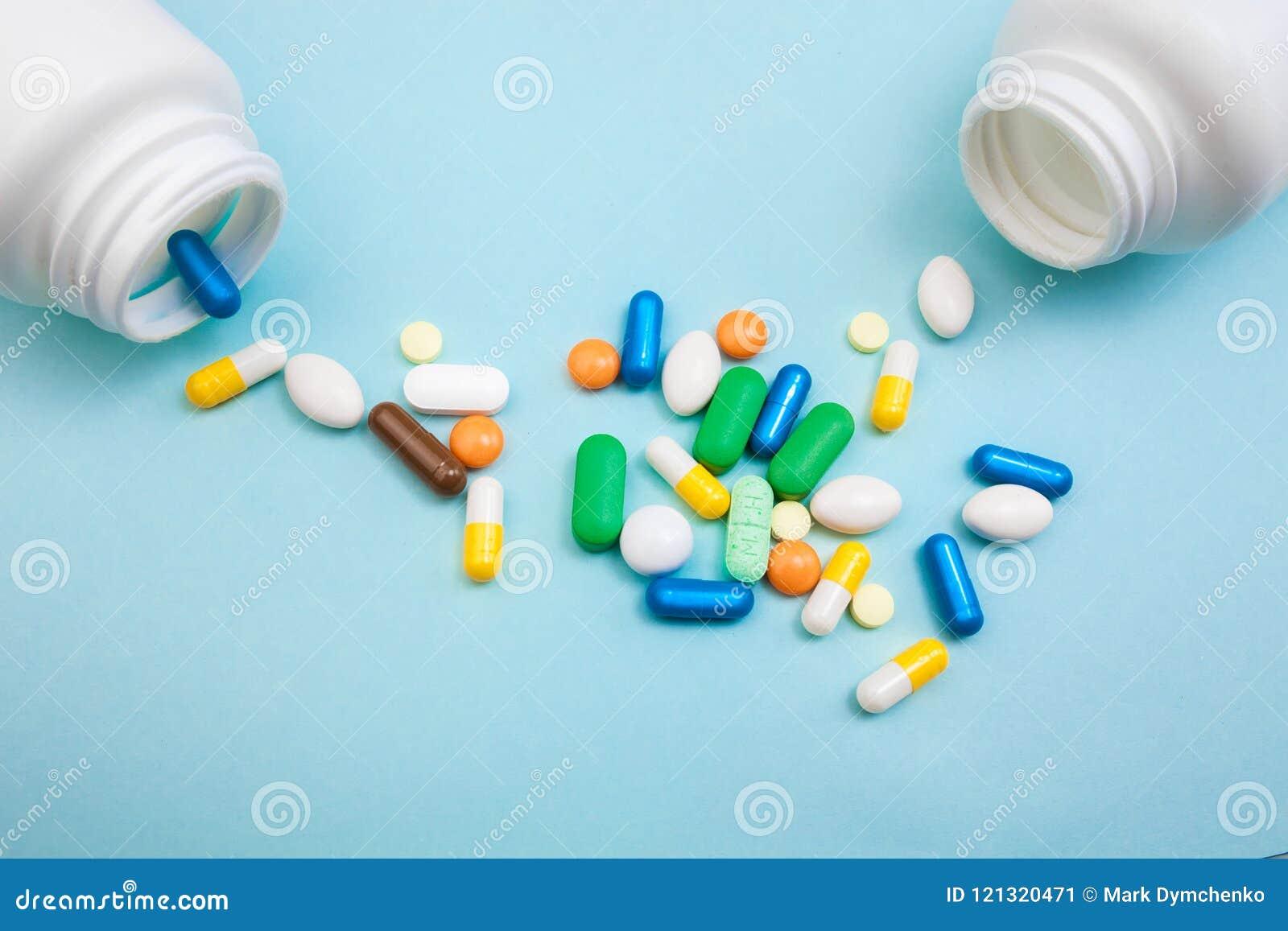 Tabletas y cápsulas multicoloras, botella blanca para las tabletas, píldoras farmacéuticas de la medicina en el fondo azul, una a