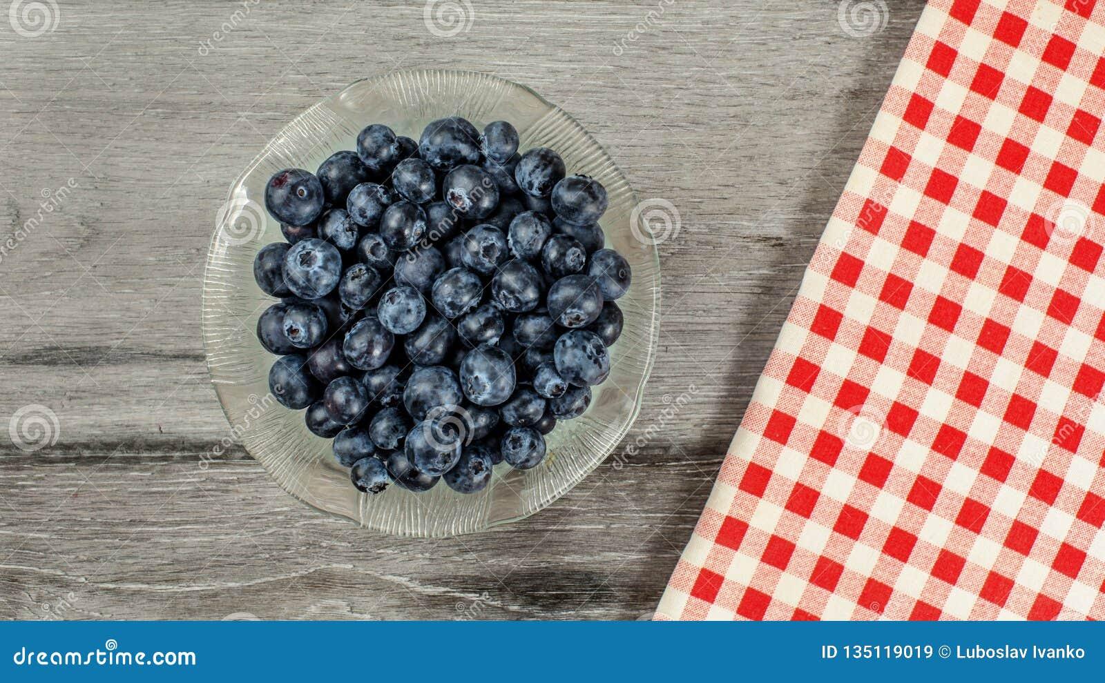 Tabletop sikt, liten exponeringsglasbunke av blåbär, röd rutig ginghambordduk bredvid den på det gråa träskrivbordet