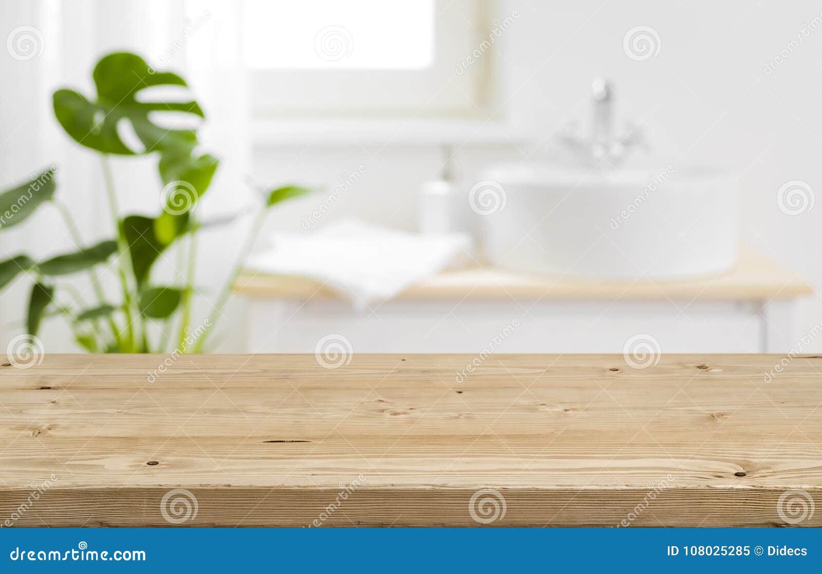 Tabletop vazio para a exposição do produto com fundo borrado do interior do banheiro