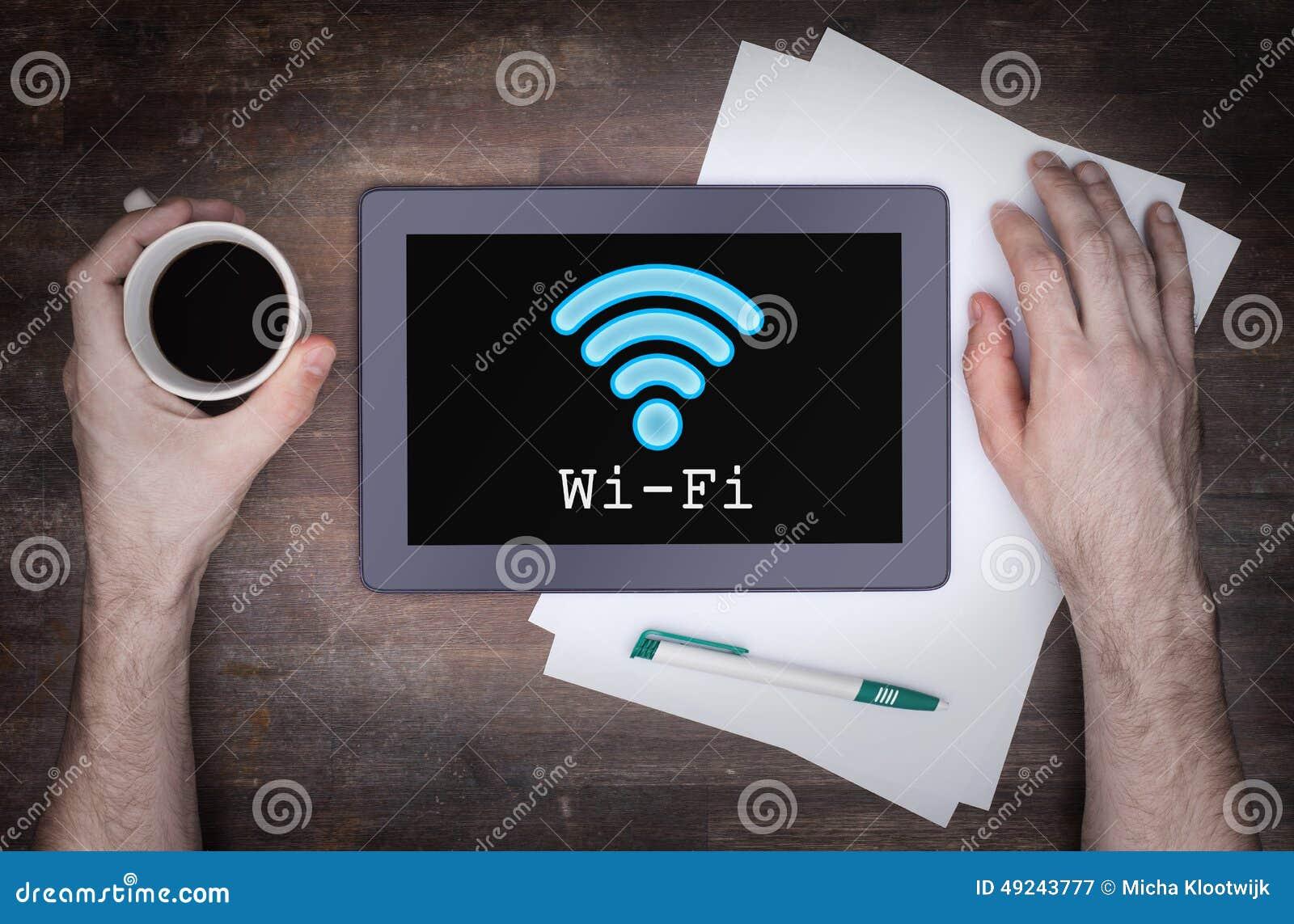 Tablette avec la connexion de wi fi sur un bureau en bois image