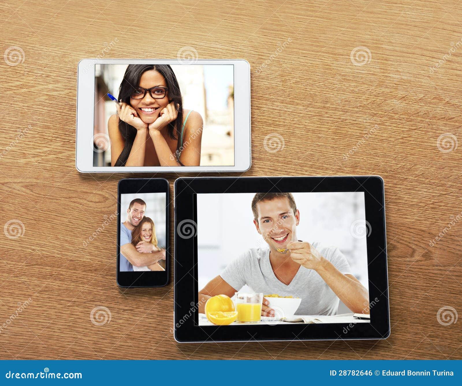 Tablettes de Digitals et téléphone intelligent avec des images sur un bureau