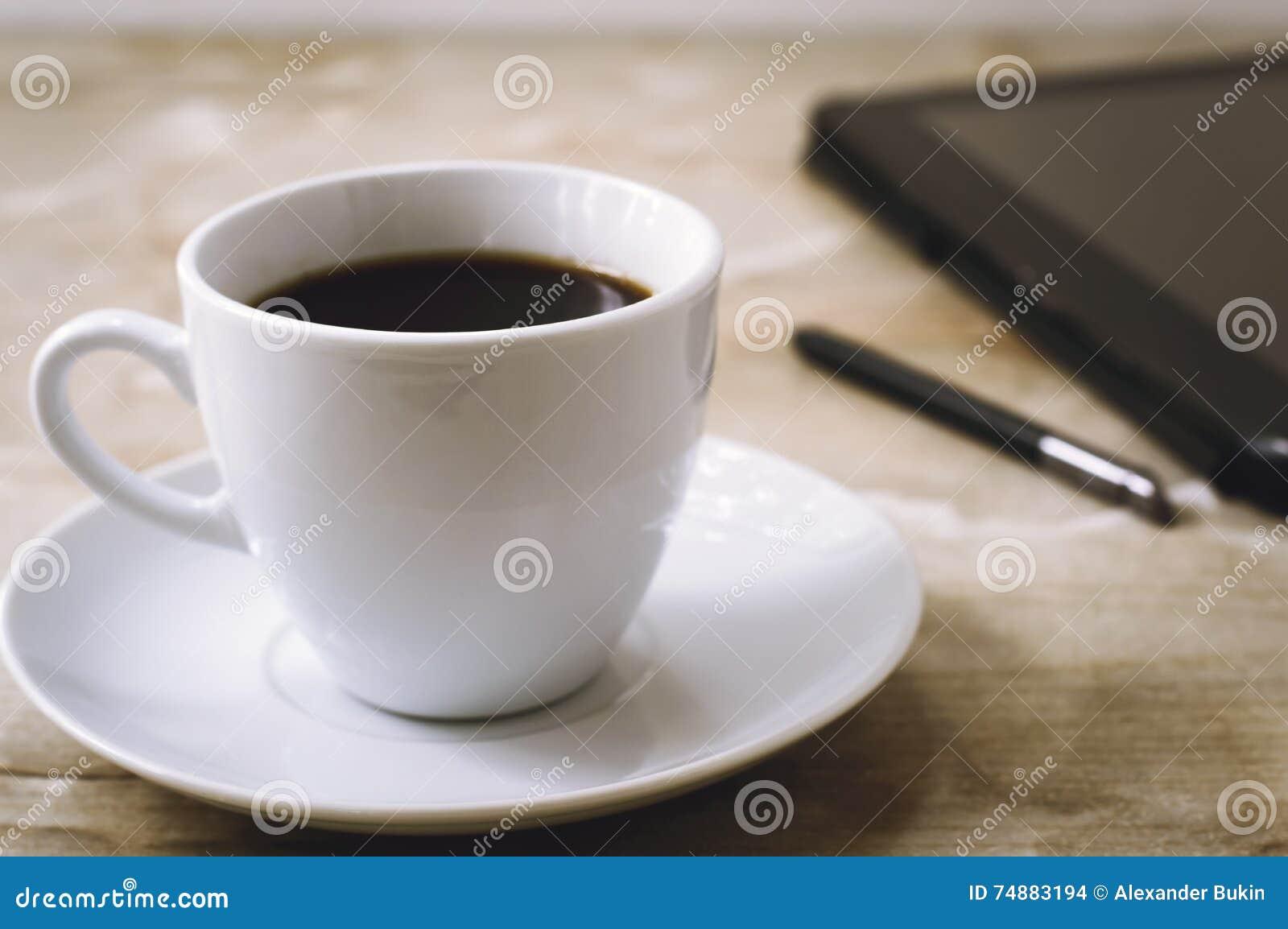 A tabuleta com um estilete e um café preto quente