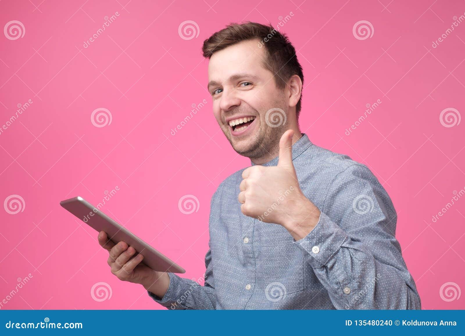 Tabuleta da terra arrendada do homem que aumenta os polegares acima e que sorri amplamente, dando a reação positiva