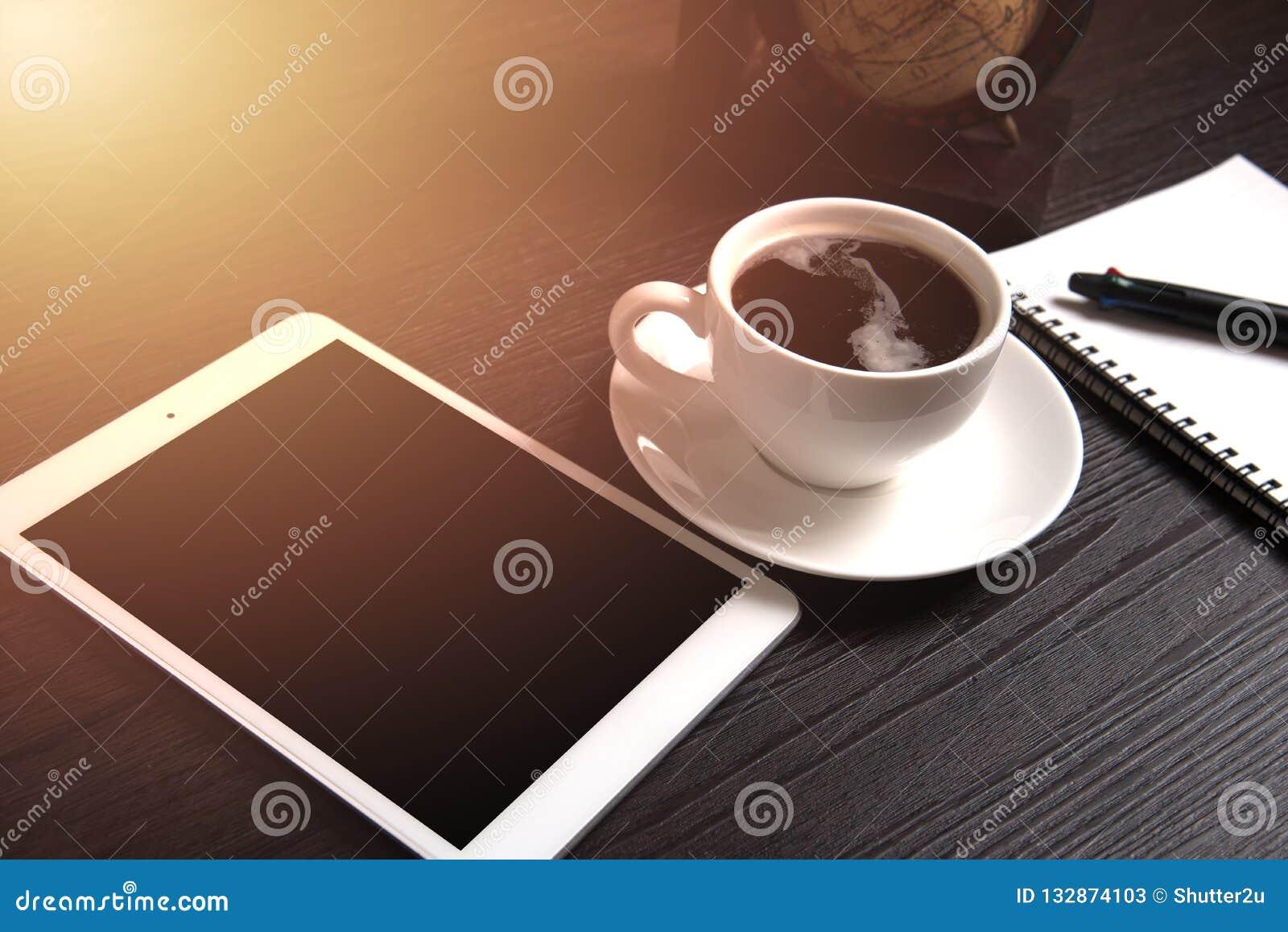 Tabuleta e café preto na tabela de madeira com o mundo da terra de Digitas