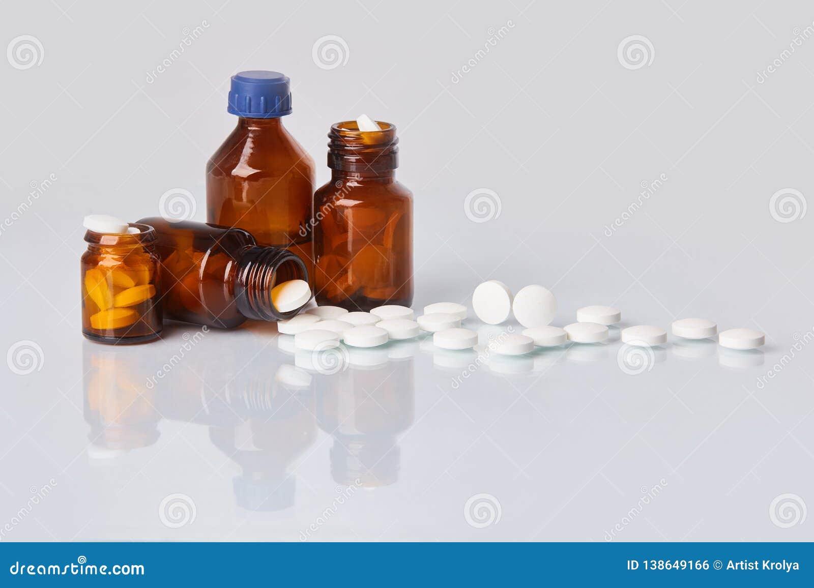 Tabuletas e comprimidos brancos na garrafa de vidro escura no fundo branco