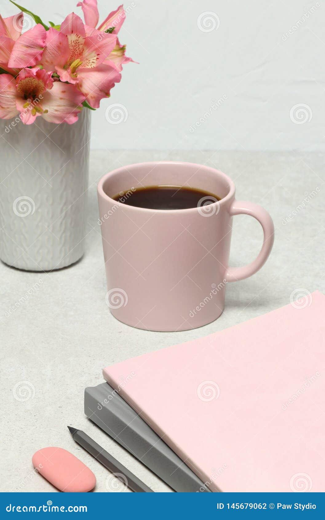 Taccuini, matita, tazza di caffè, fiori del mazzo sulla tavola di pietra