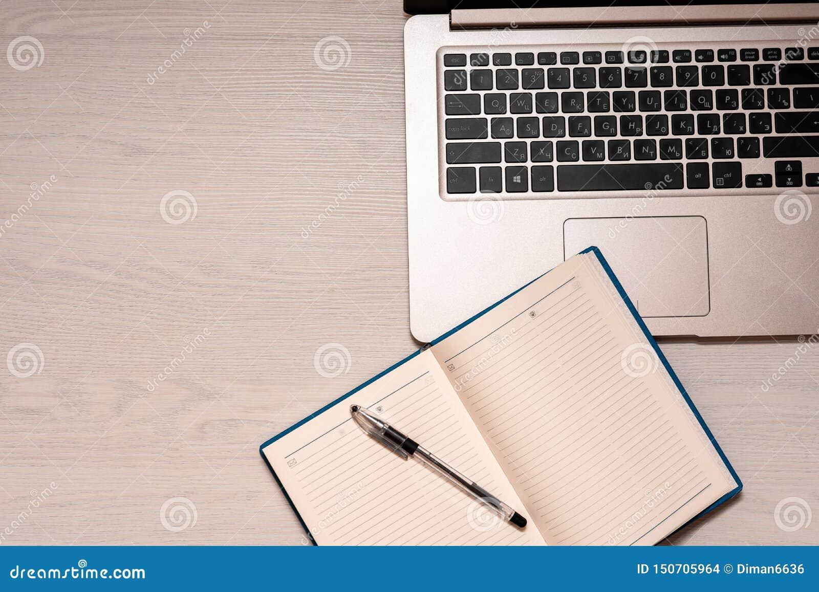 Taccuino aperto con la penna nera ed il computer portatile d argento su una tavola di legno bianca, vista superiore, spase della