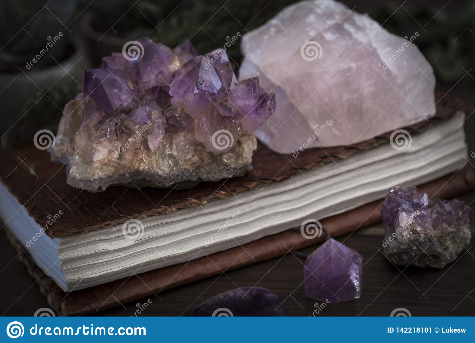 Taccuino chiuso o giornale con l ametista e Rose Quartz Crystals sulla cima