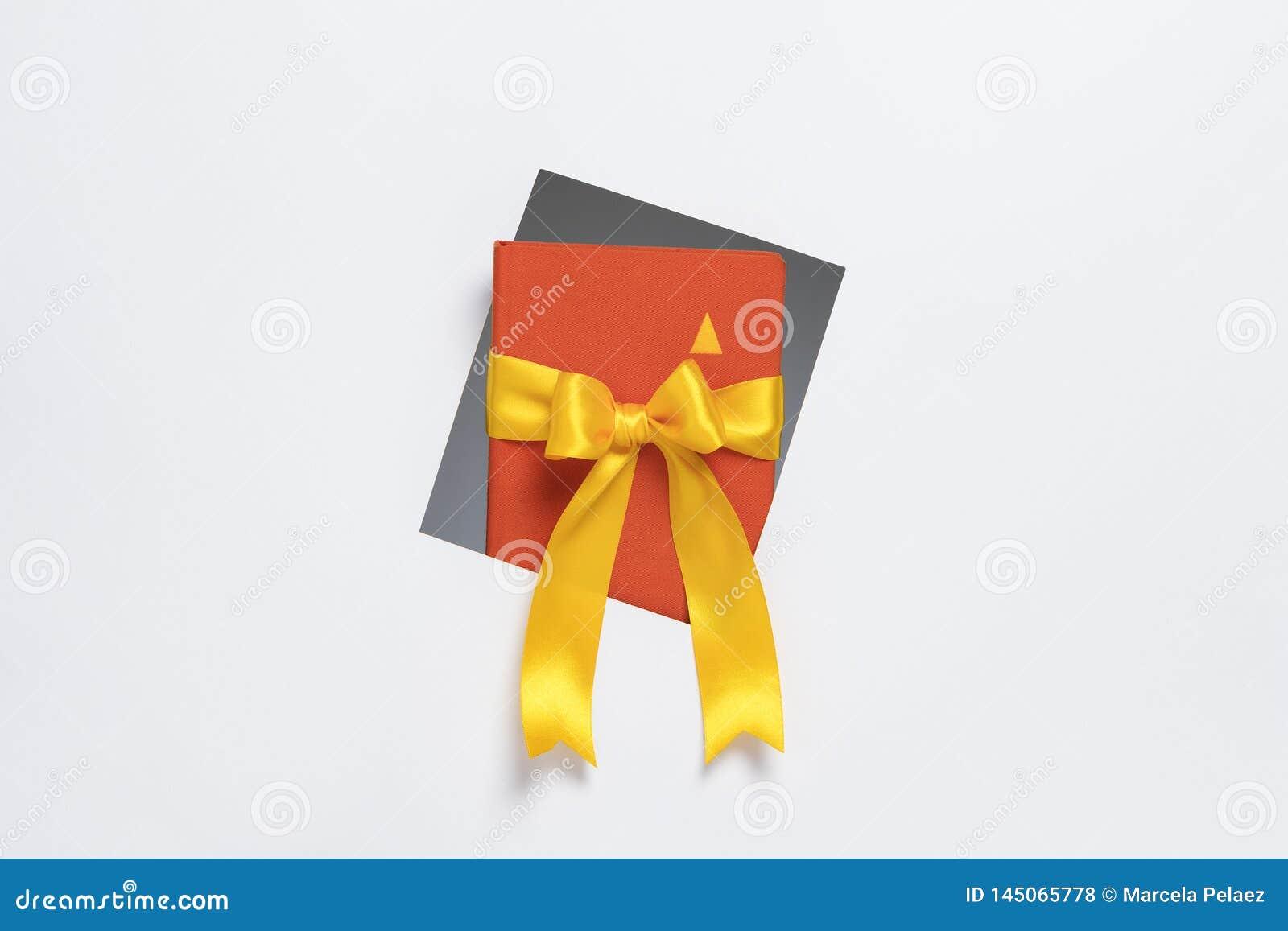 Taccuino con il nastro del regalo che esce da struttura su fondo bianco
