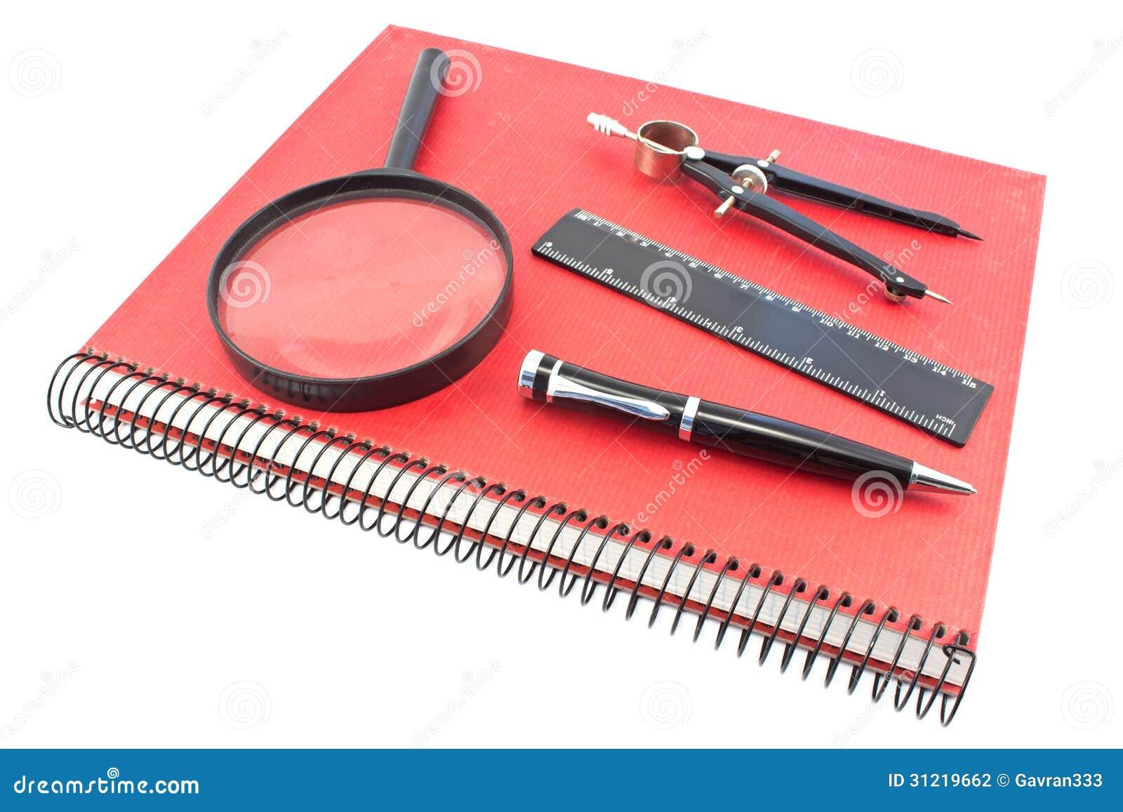 Taccuino con la bussola di disegno, il righello, la penna e il magn