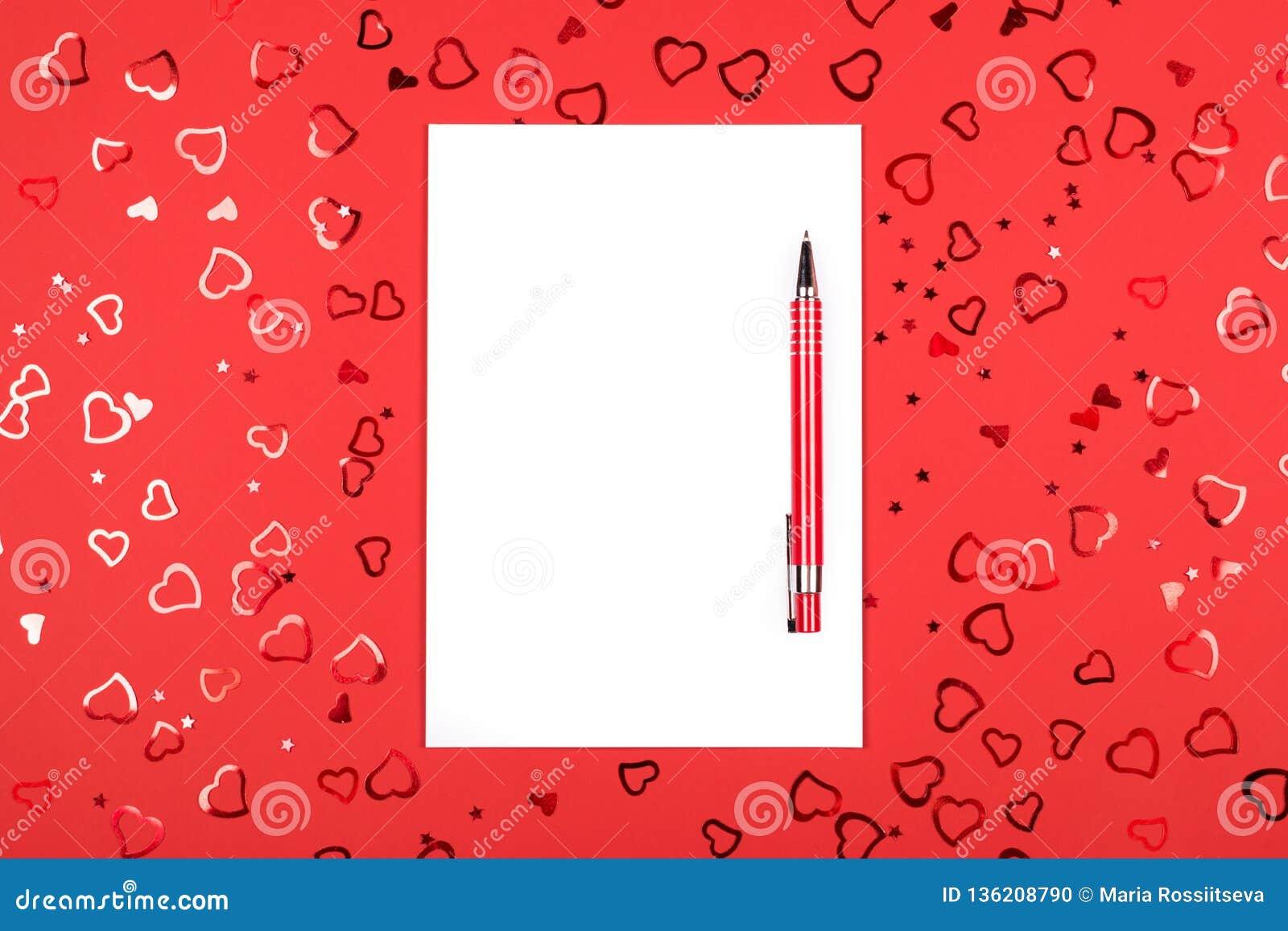 Taccuino con la penna su fondo rosso con i coriandoli in forma di cuore