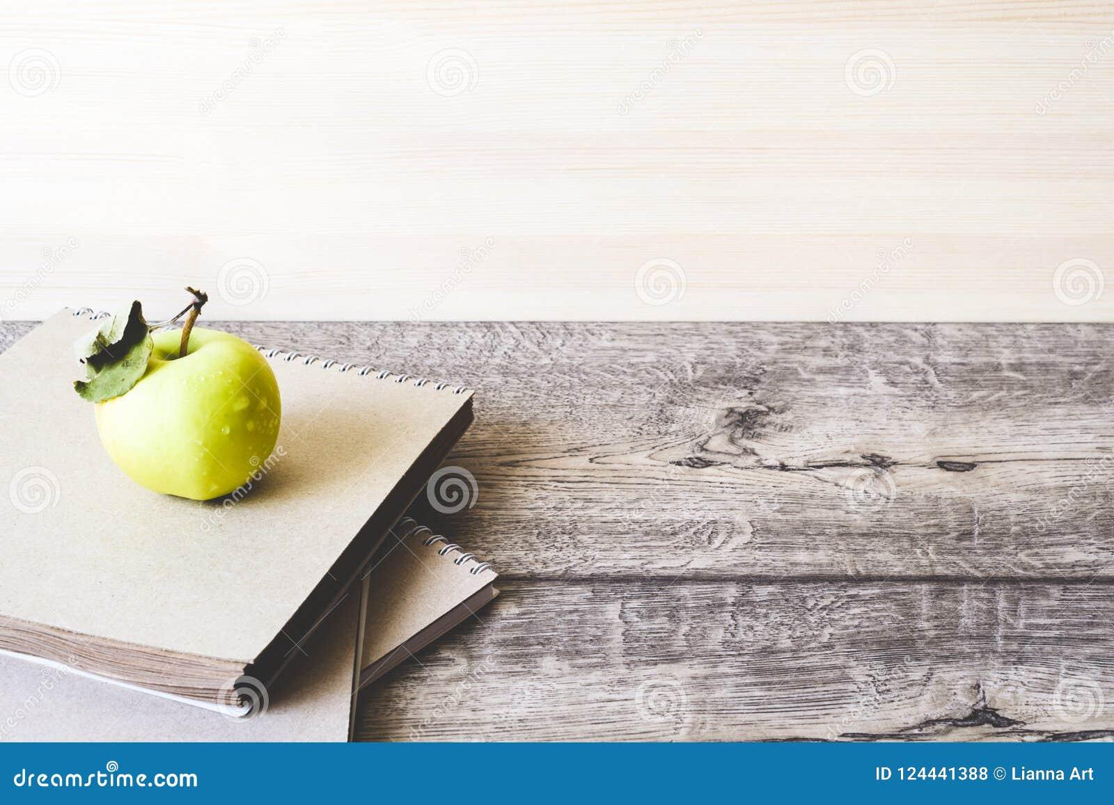 Taccuino e mela della scuola su fondo di legno