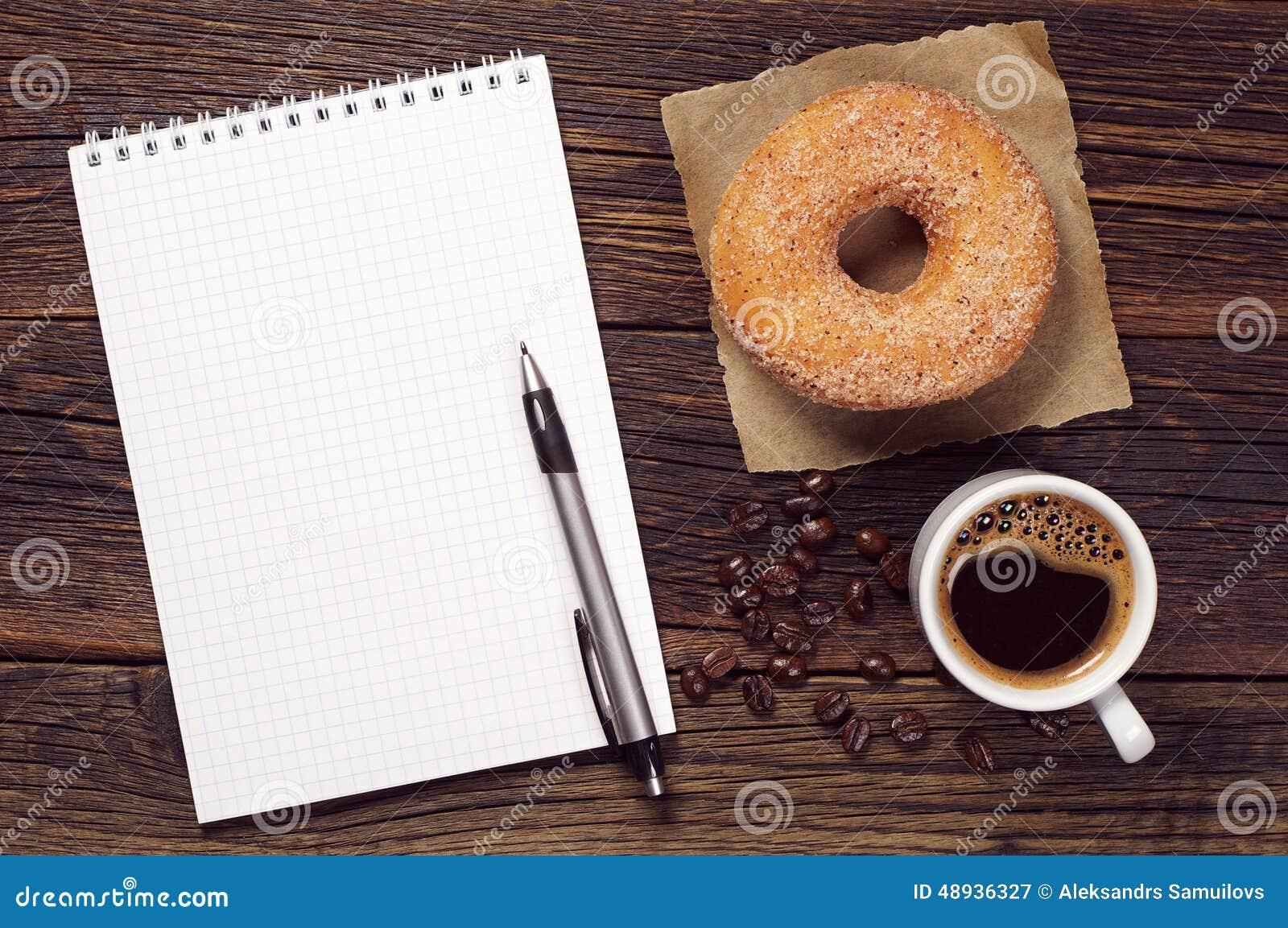 Taccuino e tazza di caffè con la ciambella