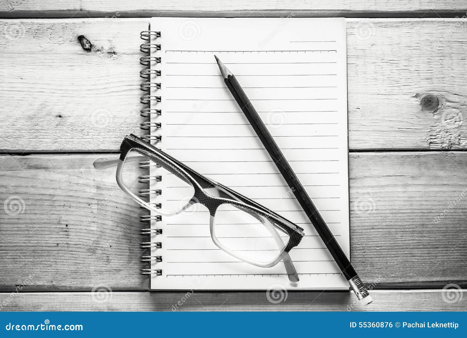 Taccuino, matita ed occhiali sulla tavola di legno