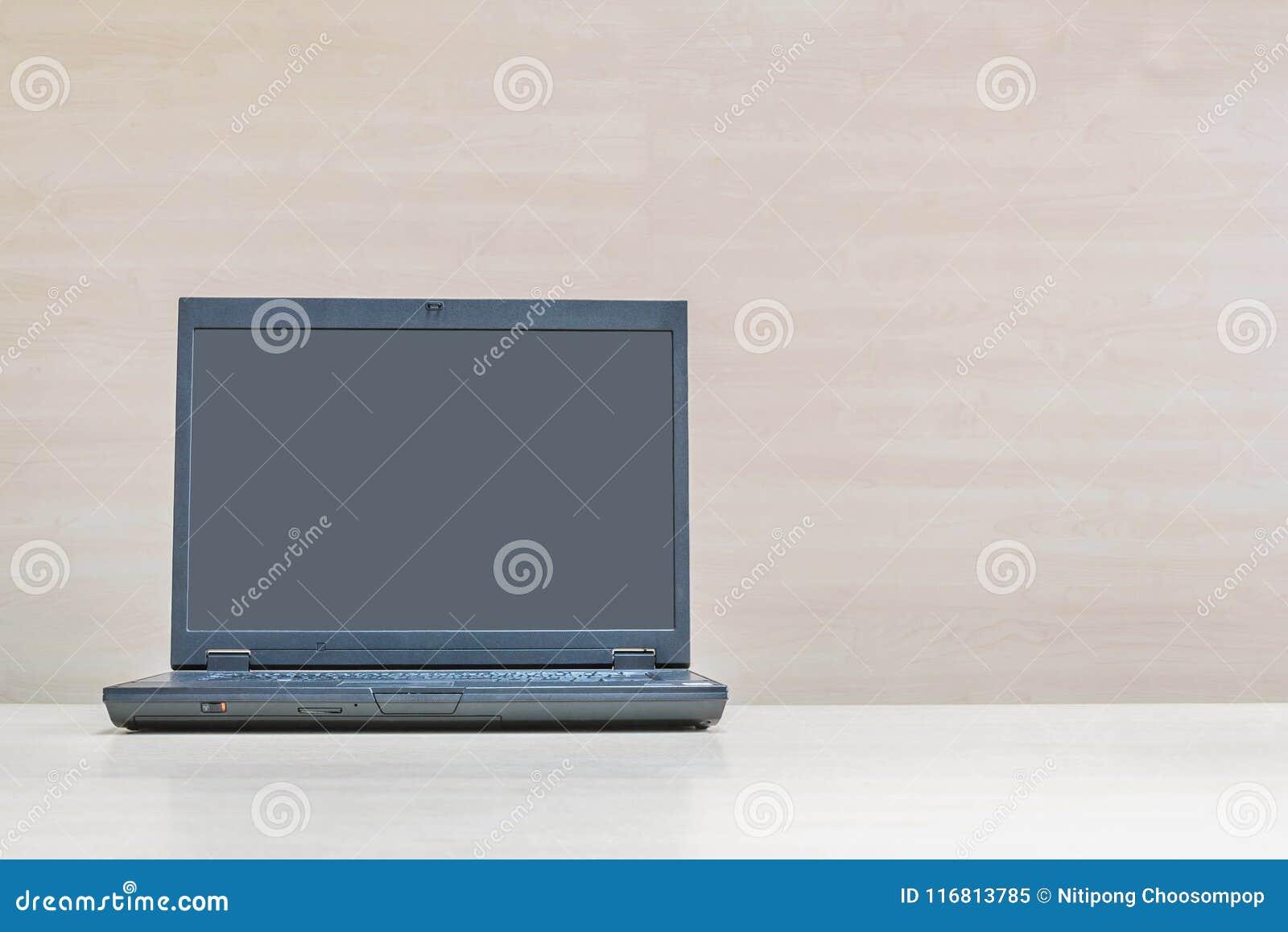 Taccuino nero del computer del primo piano sulla parete di legno vaga di legno e dello scrittorio nel fondo di struttura della sa