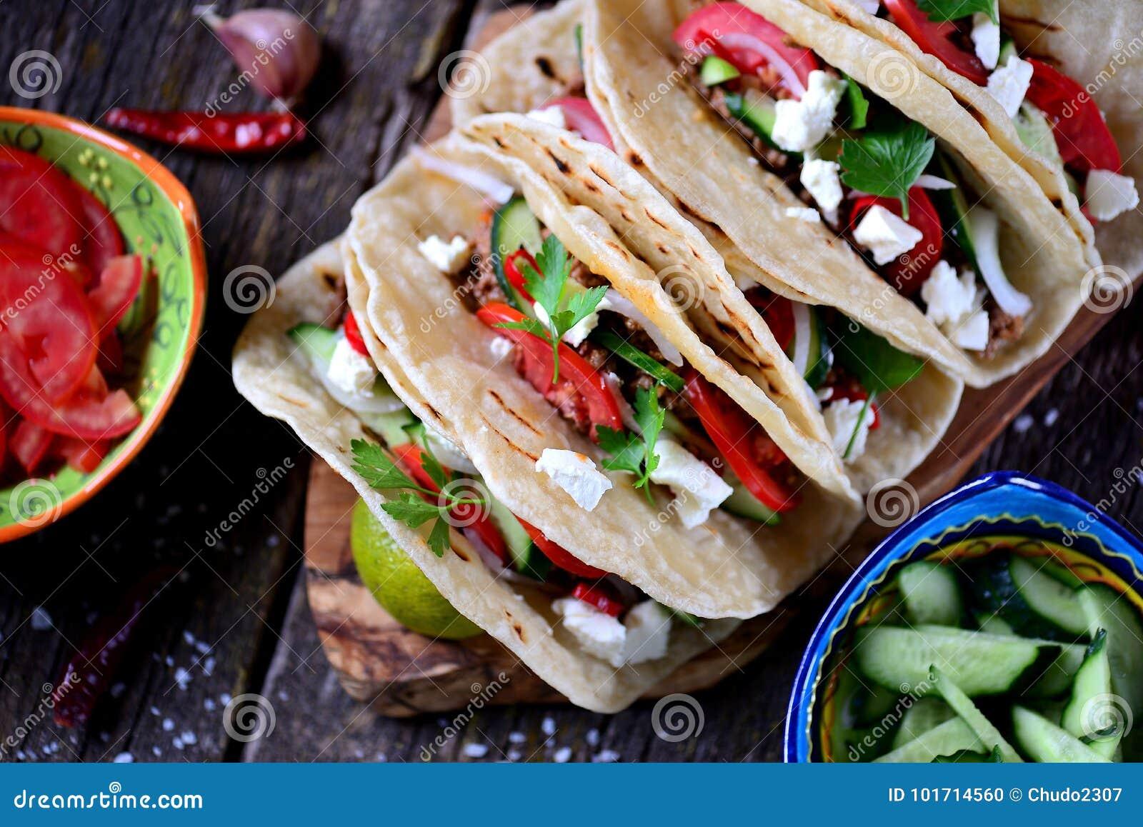 Tacos caseiros com carne triturada no molho de tomate com tomates frescos, pepinos, pimentão e queijo macio Alimento mexicano