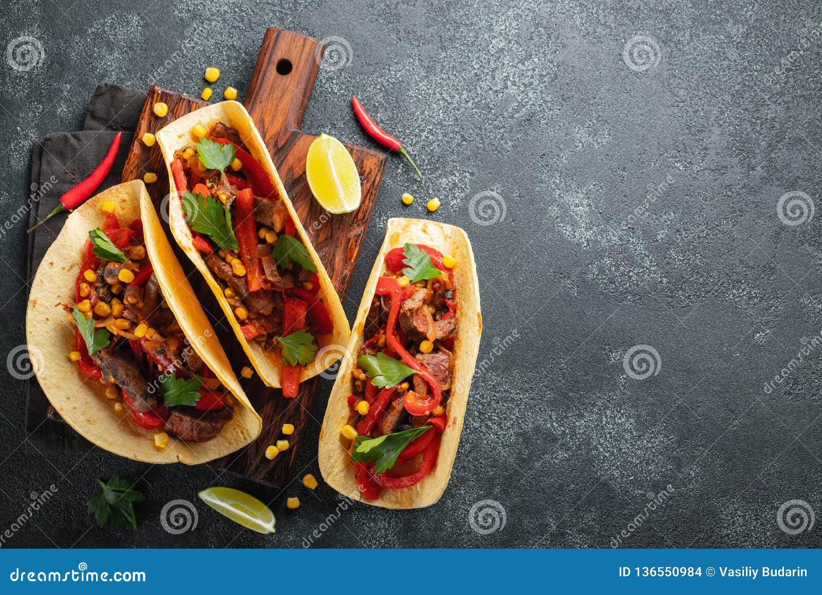 Tacos mexicain avec du boeuf, les légumes et le Salsa Pasteur d Al de Tacos sur le conseil en bois sur le fond noir Vue supérieur
