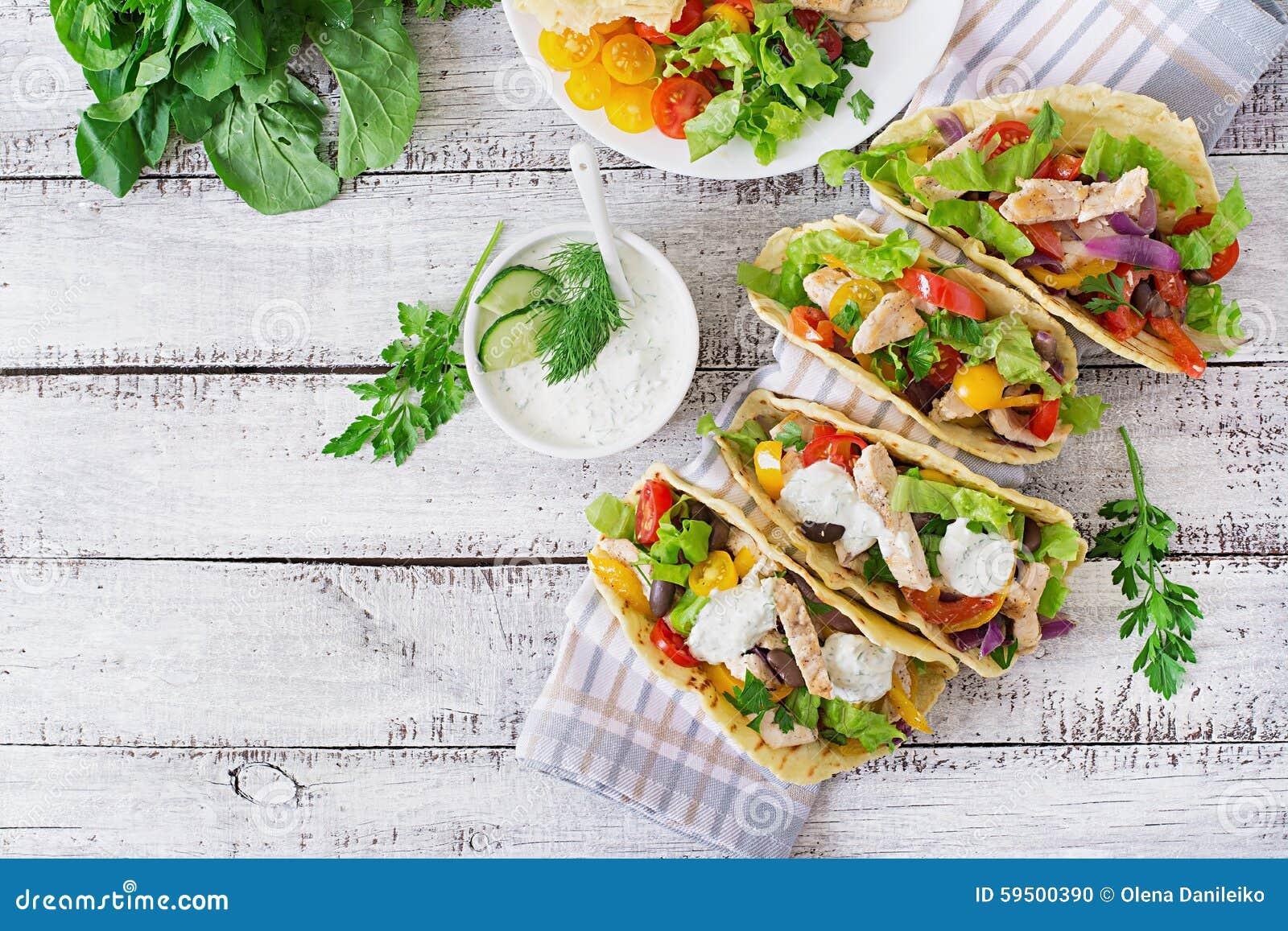 Tacos mexicanos com galinha, feijões pretos e legumes frescos e molho de tártaro