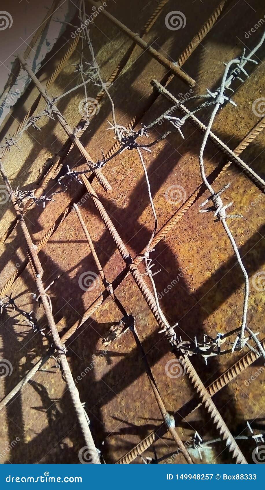 Taggtråd på metallförstärkningen på en bakgrund av rostigt järn
