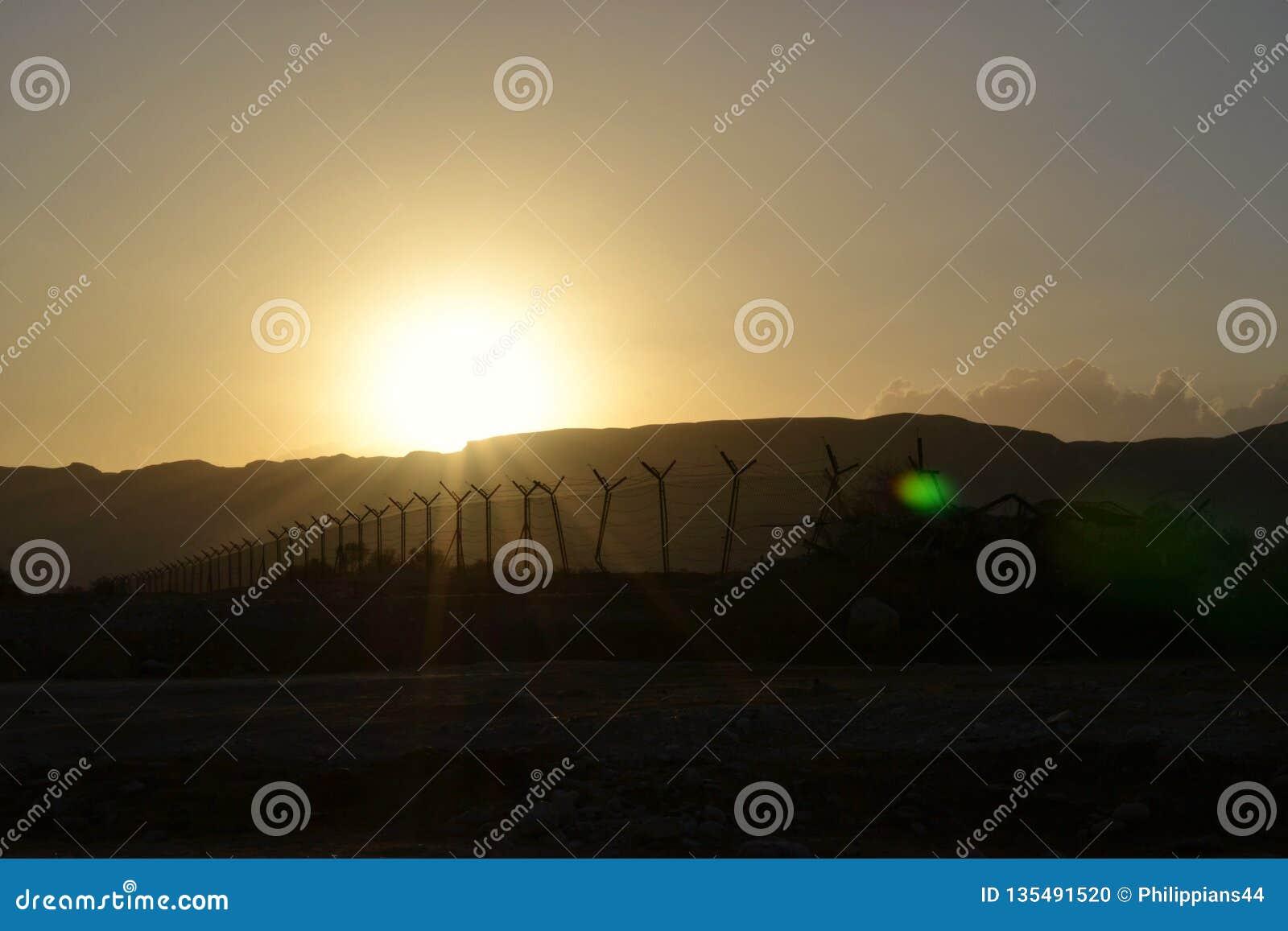 Taggtrådstaket på solnedgången i ökenbergområde på kusten av det döda havet, Westbank, Israel, Palestina