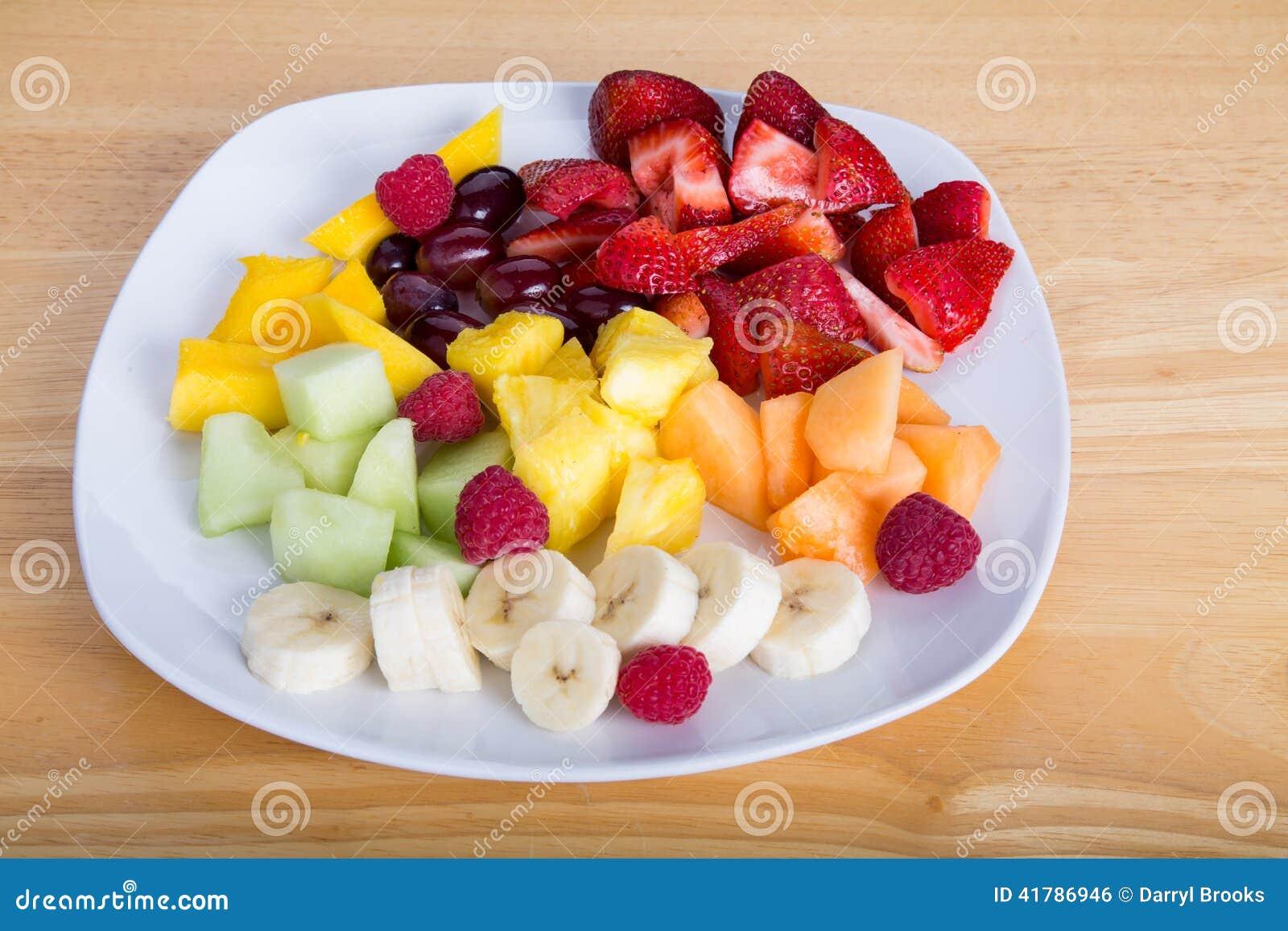 Tagli la frutta con le banane e le fragole dei manghi