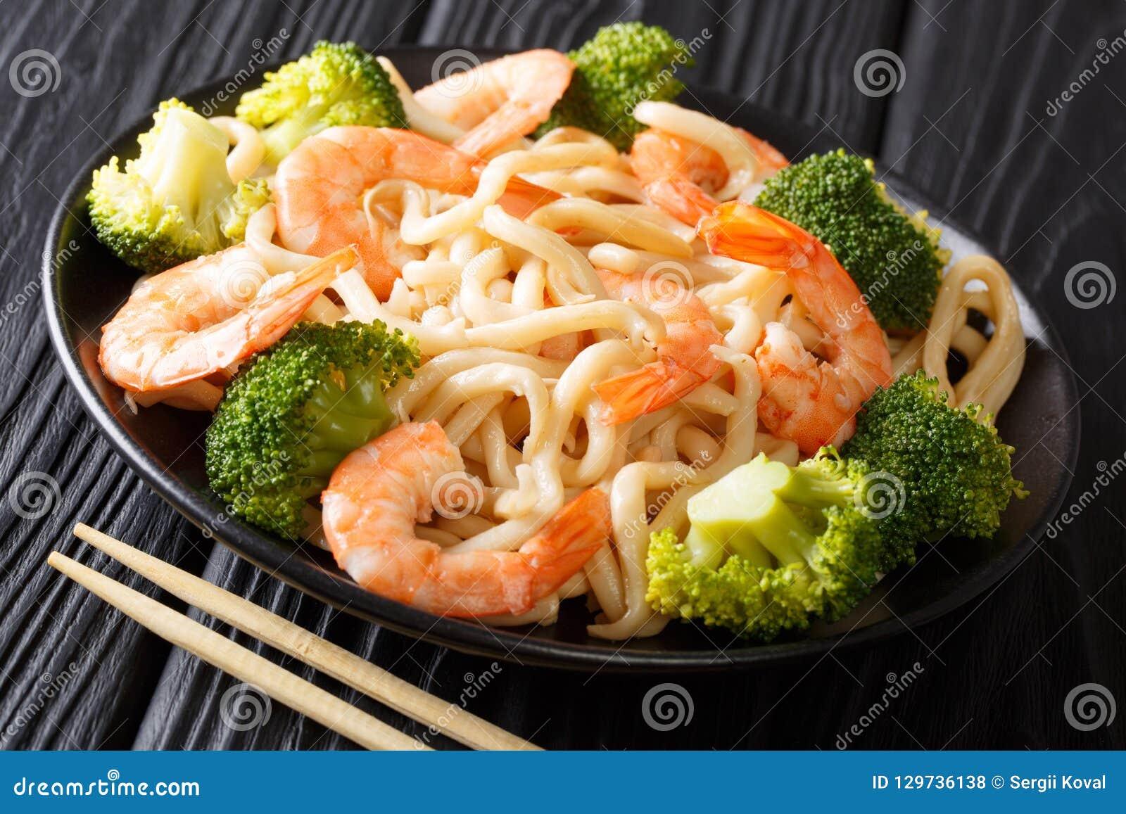 Tagliatelle asiatiche del udon di stile con i clo del gamberetto, dei broccoli e della salsa di soia