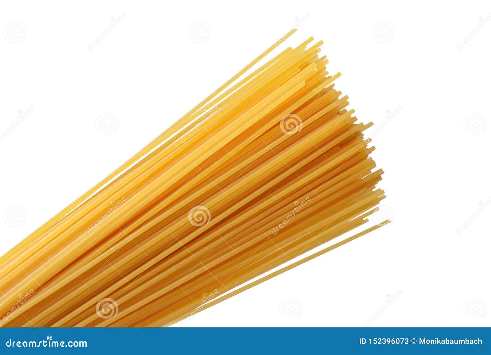 Tagliatelle gialle crude degli spaghetti del grano su fondo bianco