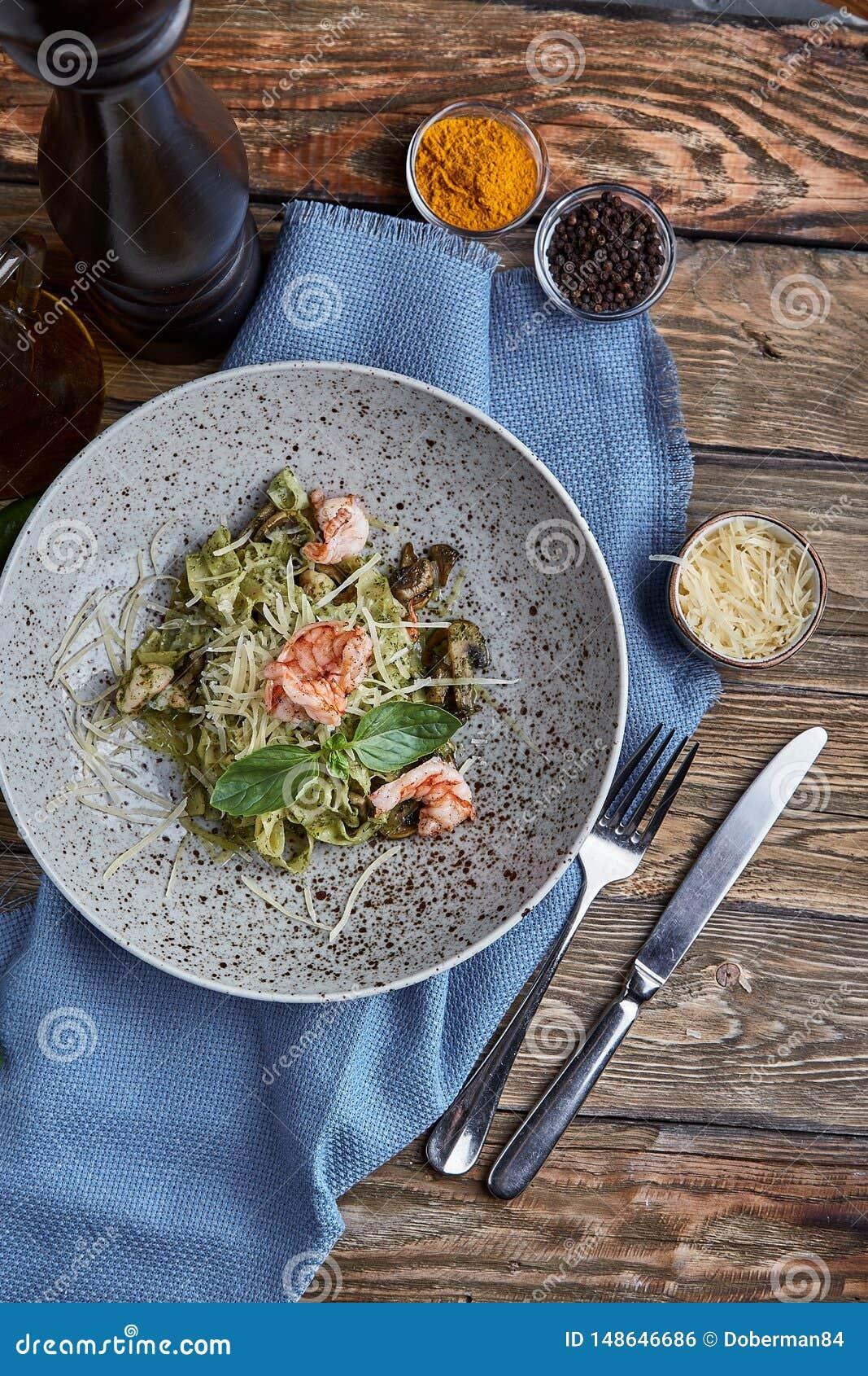 Tagliatelle med r?ka Hemlagad pasta med basilikasås och räkor och parmizan ost spelrum med lampa Begrepp