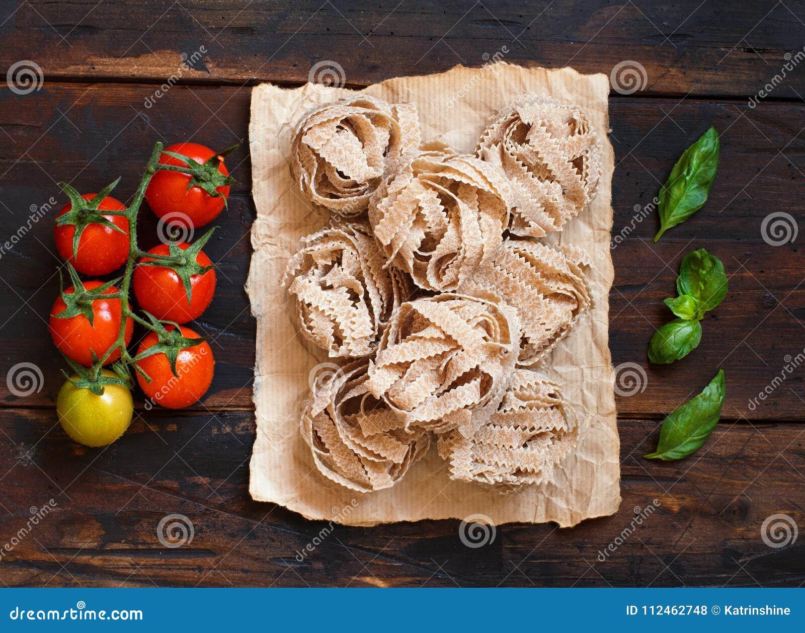 Tagliatelle, tomates e manjericão inteiros da massa do trigo