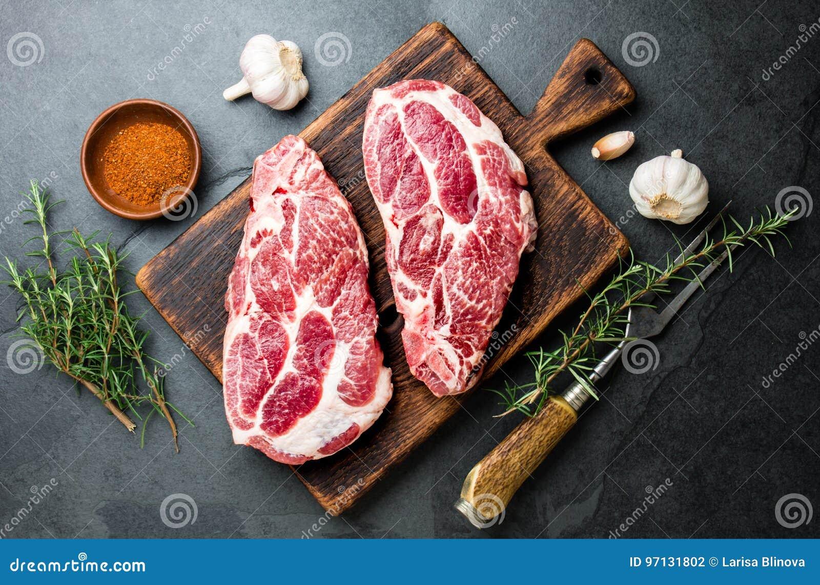 Taglio crudo della cotoletta della carne di maiale per il BBQ della griglia con le erbe sul bordo di legno, fondo dell ardesia, v
