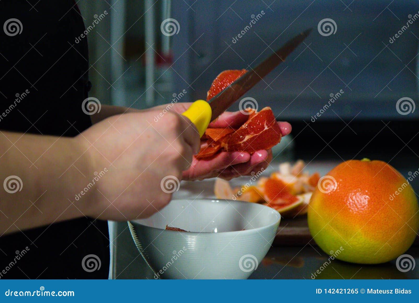 Taglio del grupefriut dal cuoco unico della cucina