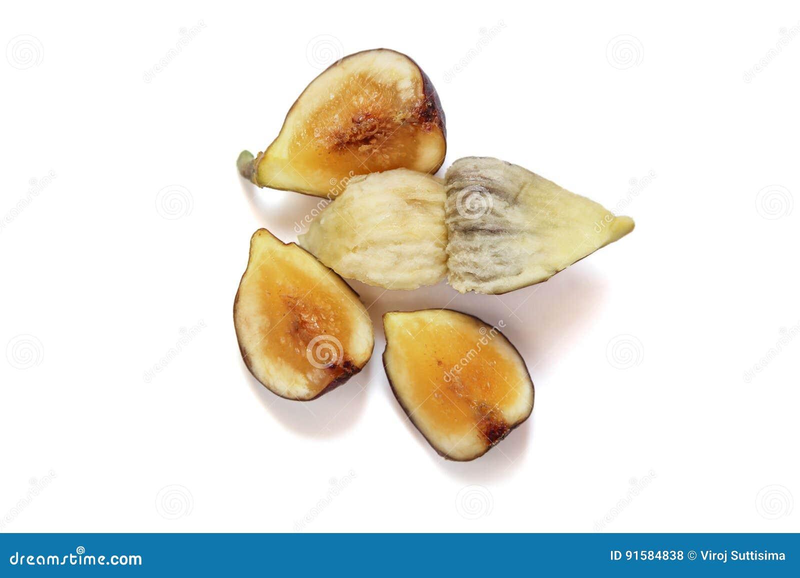 Taglio di frutti del fico da parte a parte per mostrare la carne ed i semi su fondo bianco