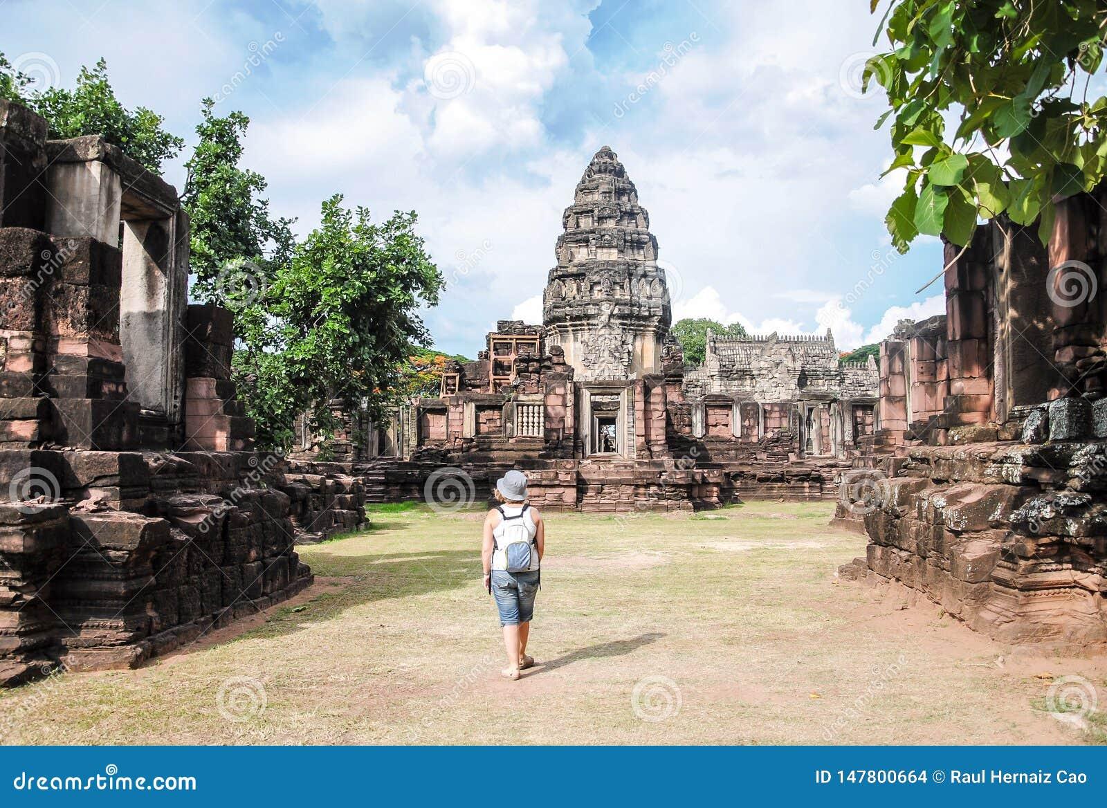 Tailândia, o 1º de junho de 2011 Turista da jovem mulher que aprecia uma vista do templo velho Prasat Hin Phimai, no parque histó
