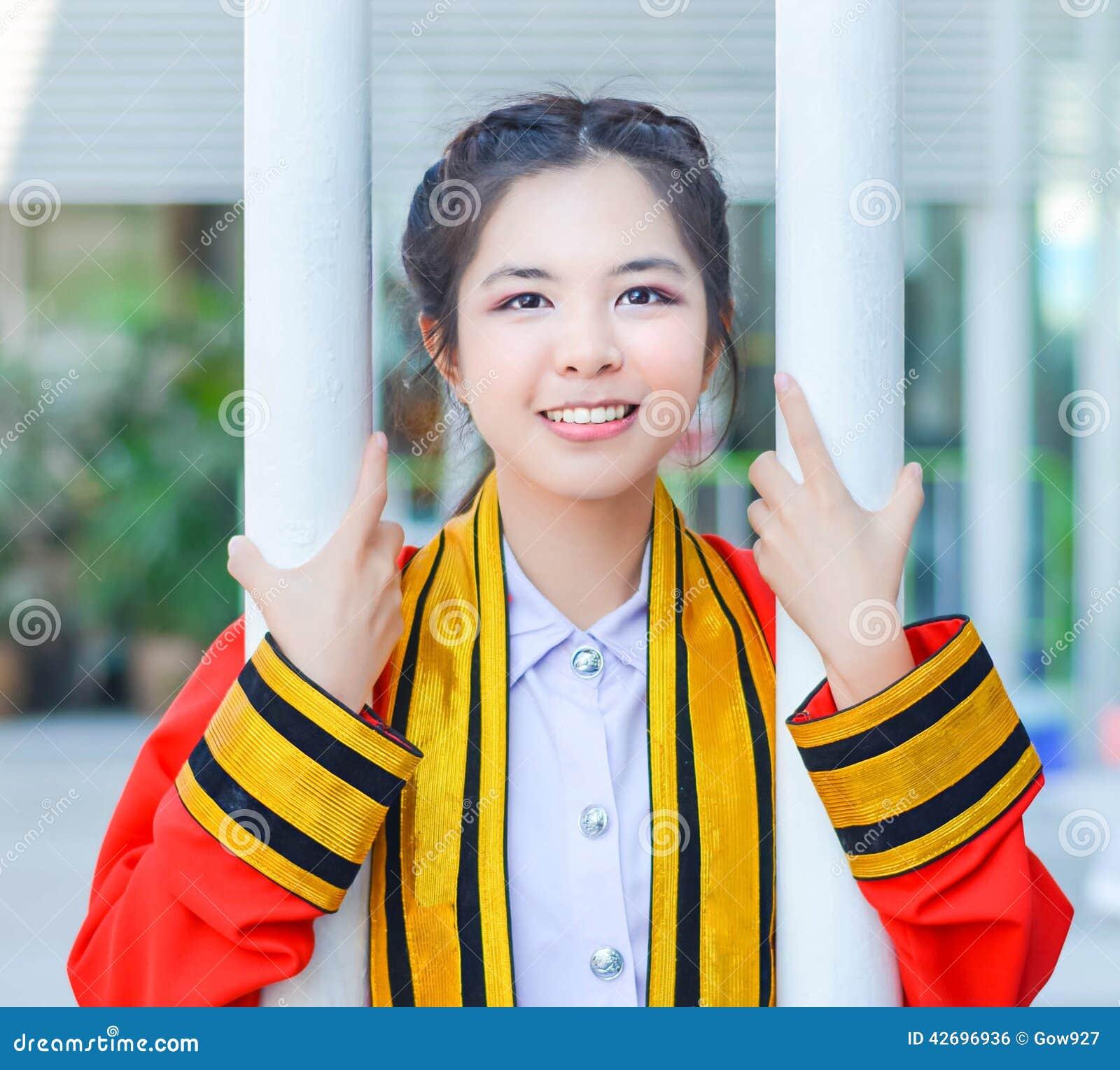 IS-IS tailandés graduado de la estudiante universitaria que sostiene polos y